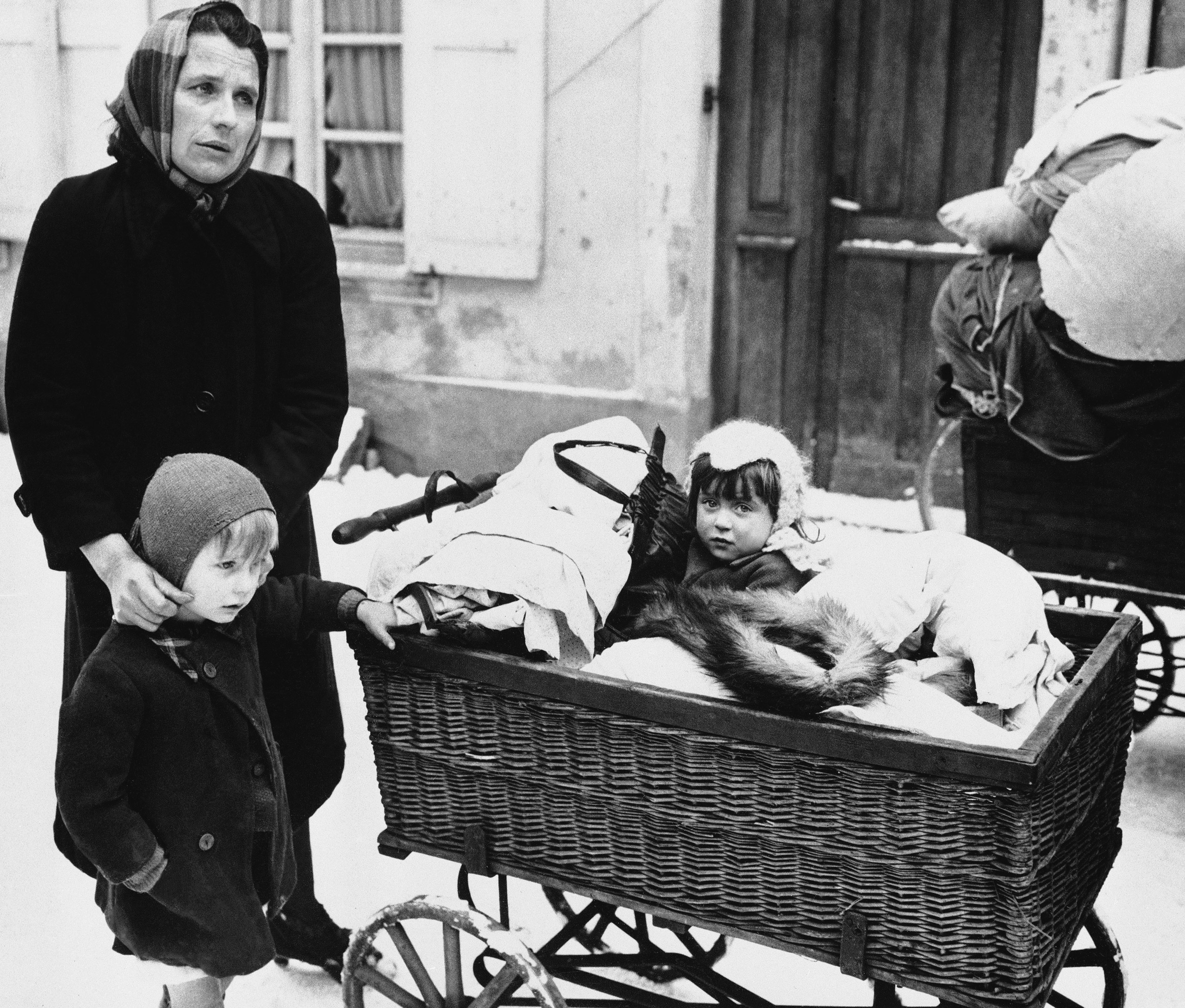 A Frenchwoman with two children and belongings loaded on a baby carriage seen in Haguenau, France on Feb. 20, 1945, before they started on their long trek to a safe rear area.  They are some of the refugees leaving the town because of the planned withdrawal of the 7th U.S. Army.