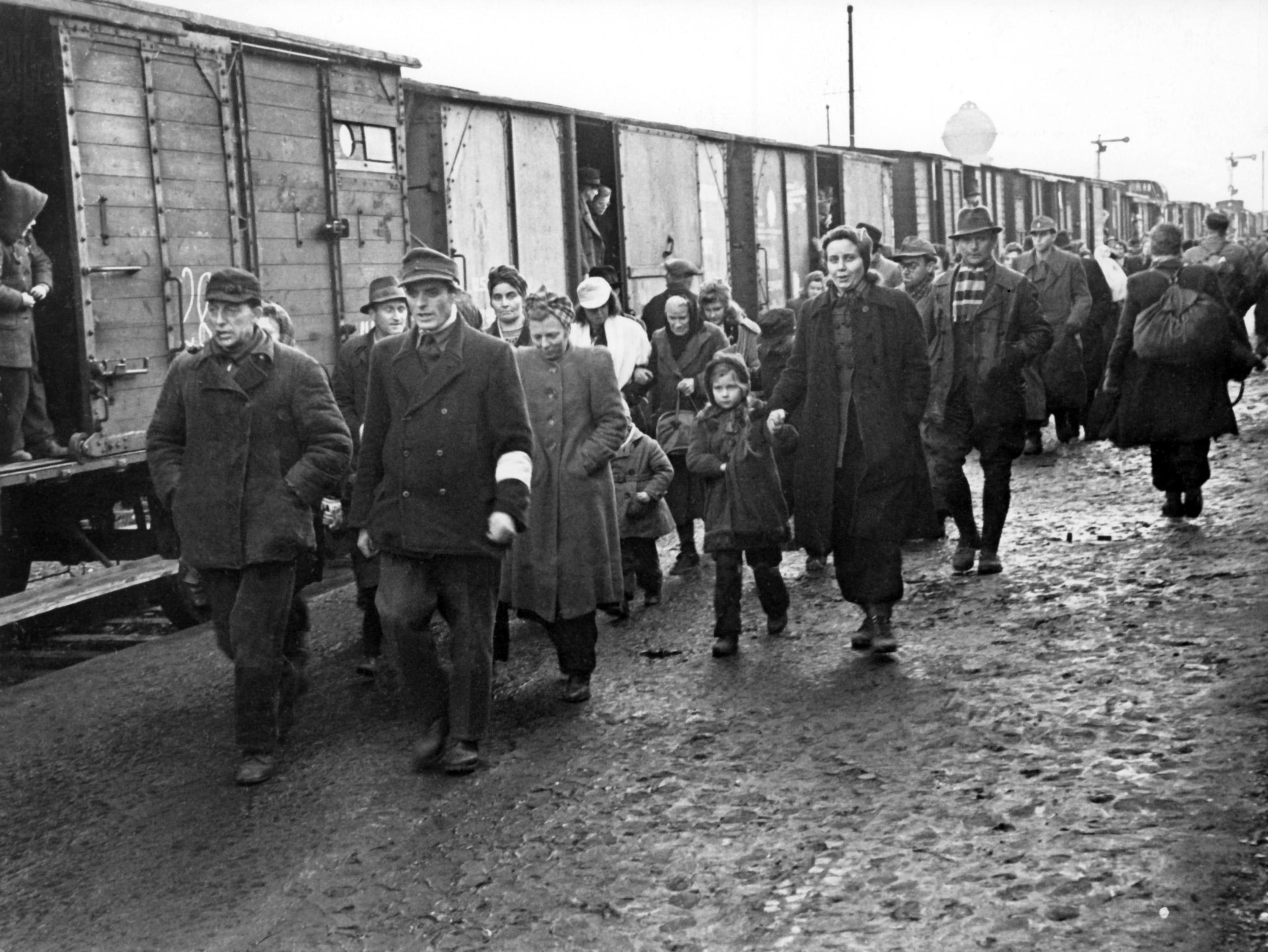 An attendant with white brassard (front, r) accompanies newly arrived refugees, in January 1946, through the refugee camp in Bebra, Germany.