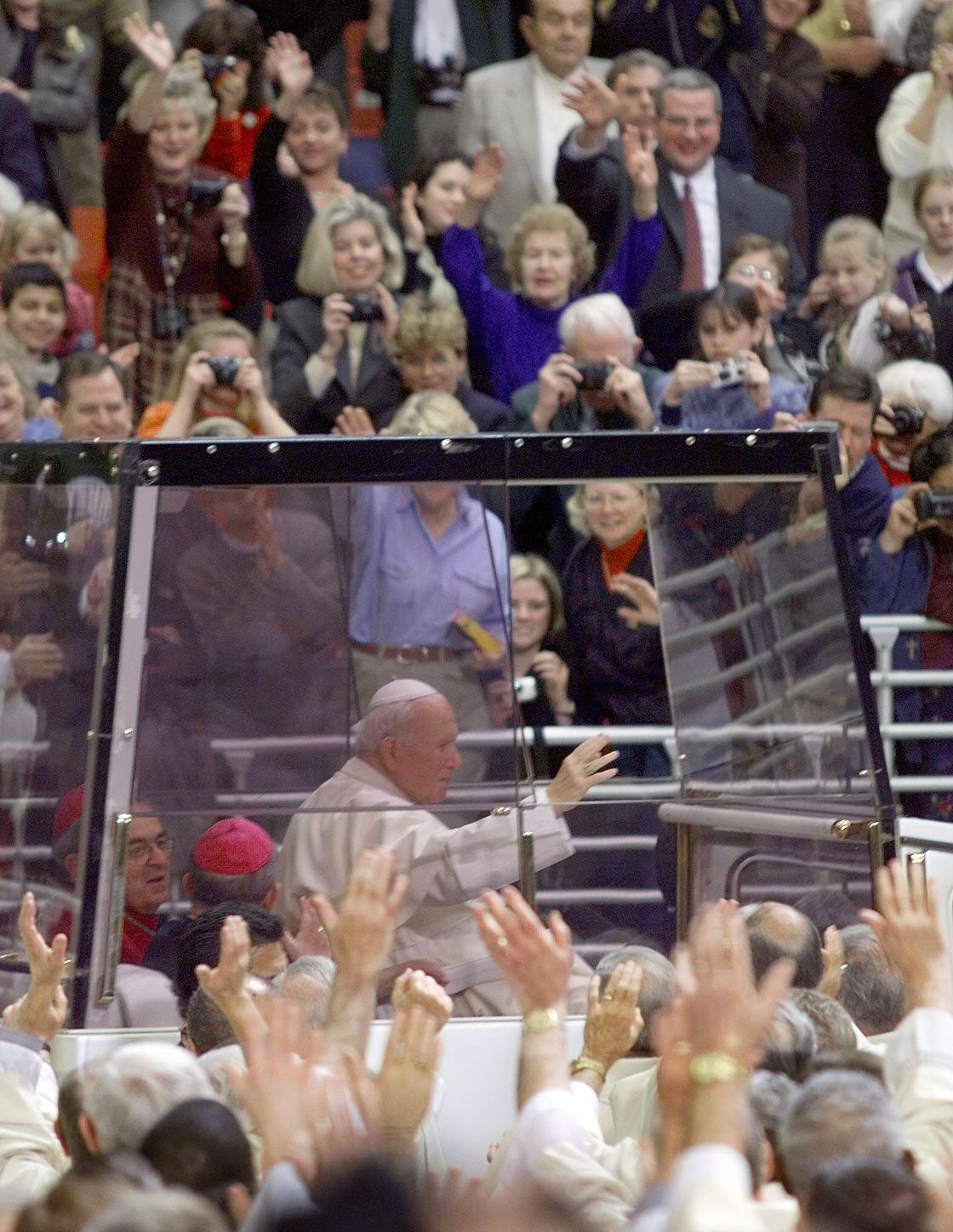 "Pope John Paul II waves to the crowd as he arrives to say Mass in his bullet-proof ""Popemobile"" in St. Louis, Mo., on Jan. 27, 1999."