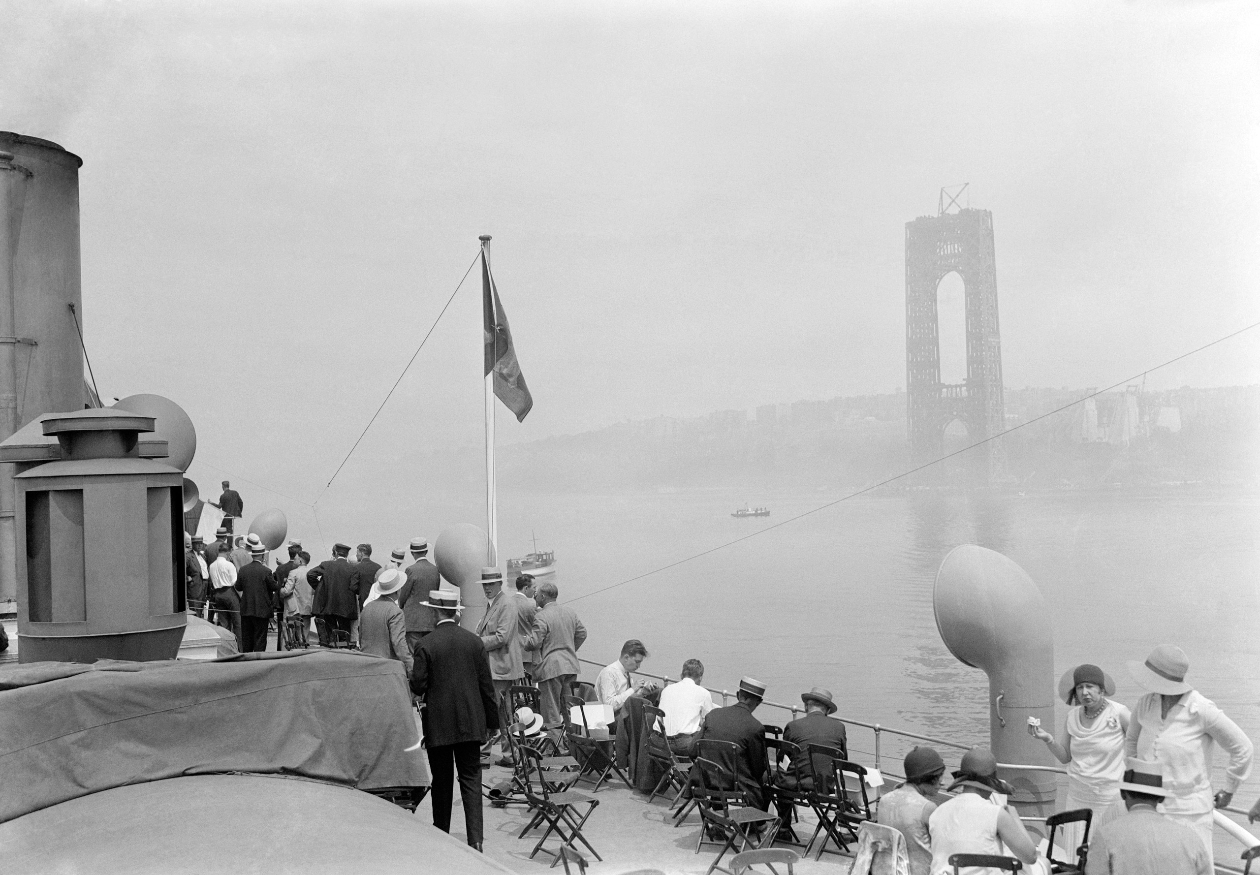 New Jersey and New York connected together by first cable of the new Hudson River Bridge at 178th Street in New York City. Photo shows a general view of the crowd on the Hudson River Day Line steamer Peter Stuyvesant watching the raising of the cable of the new Hudson River Bridge. One of the large piers of the bridge may be seen in the background to where the cable was hoisted from the river bottom.