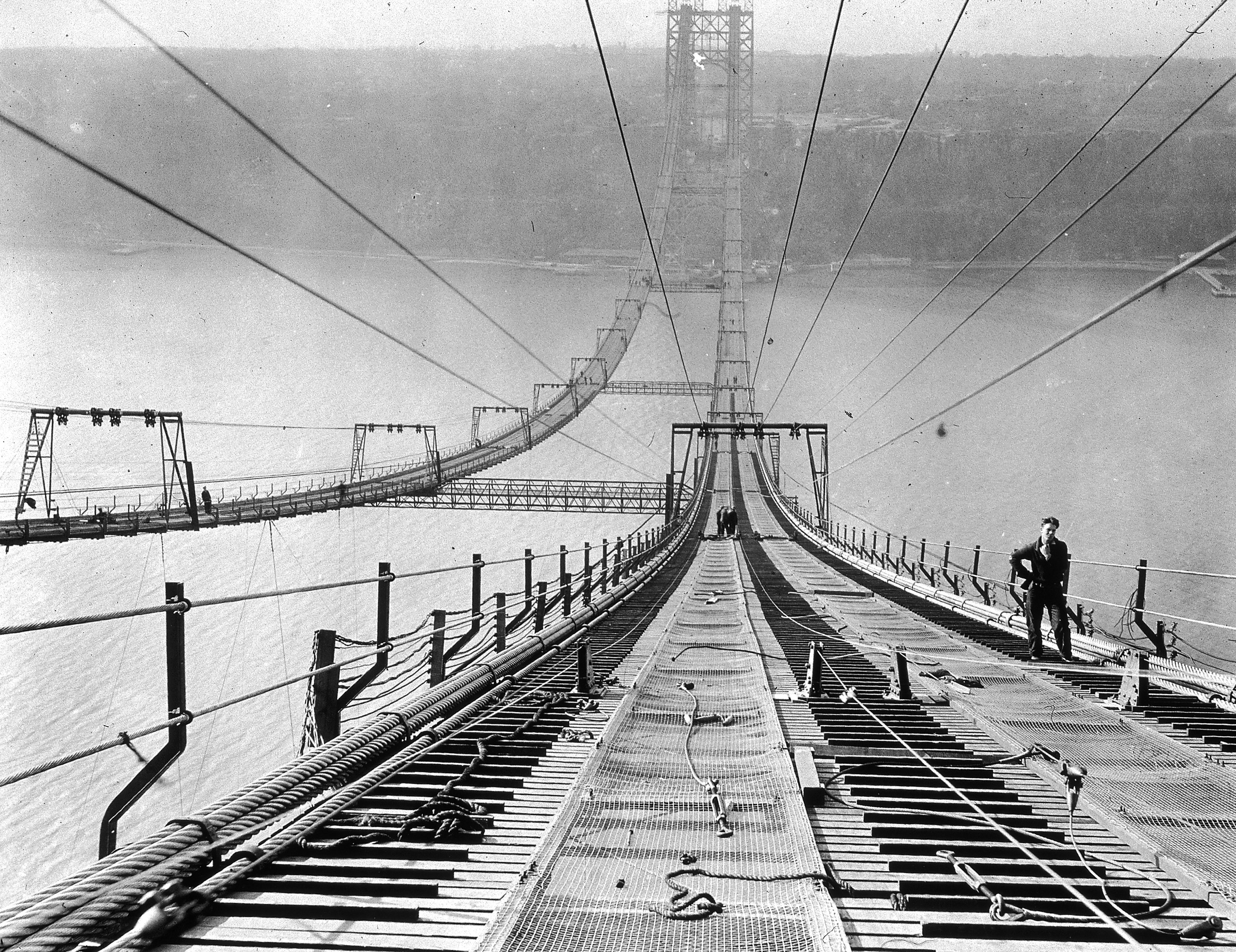 Full-length image of a worker pausing near the top of the George Washington Bridge during its construction, New York City.  Circa 1930.