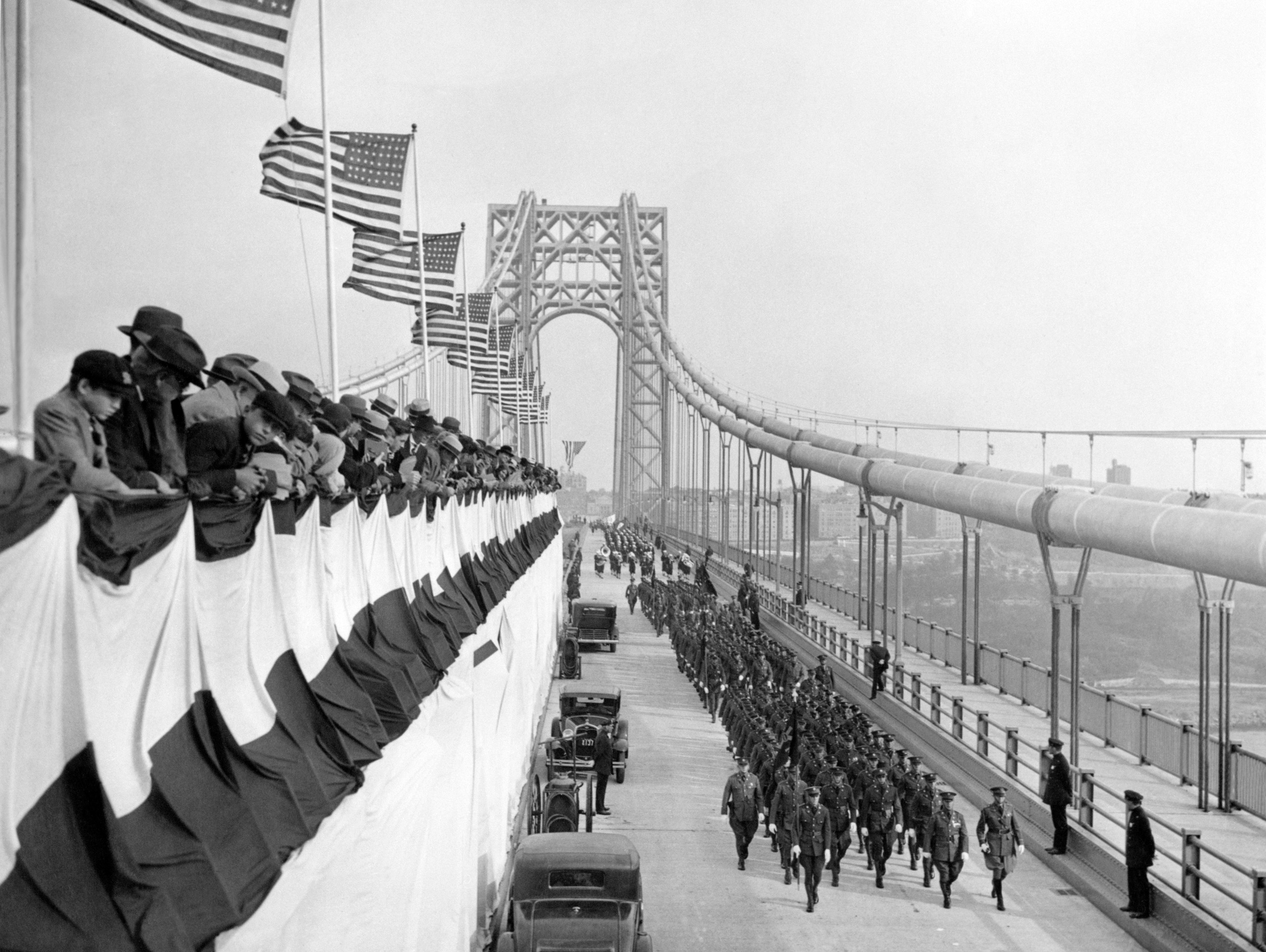 Police officers march beneath American flags during the opening ceremonies for the George Washington Bridge in New York City on Oct. 24, 1931.