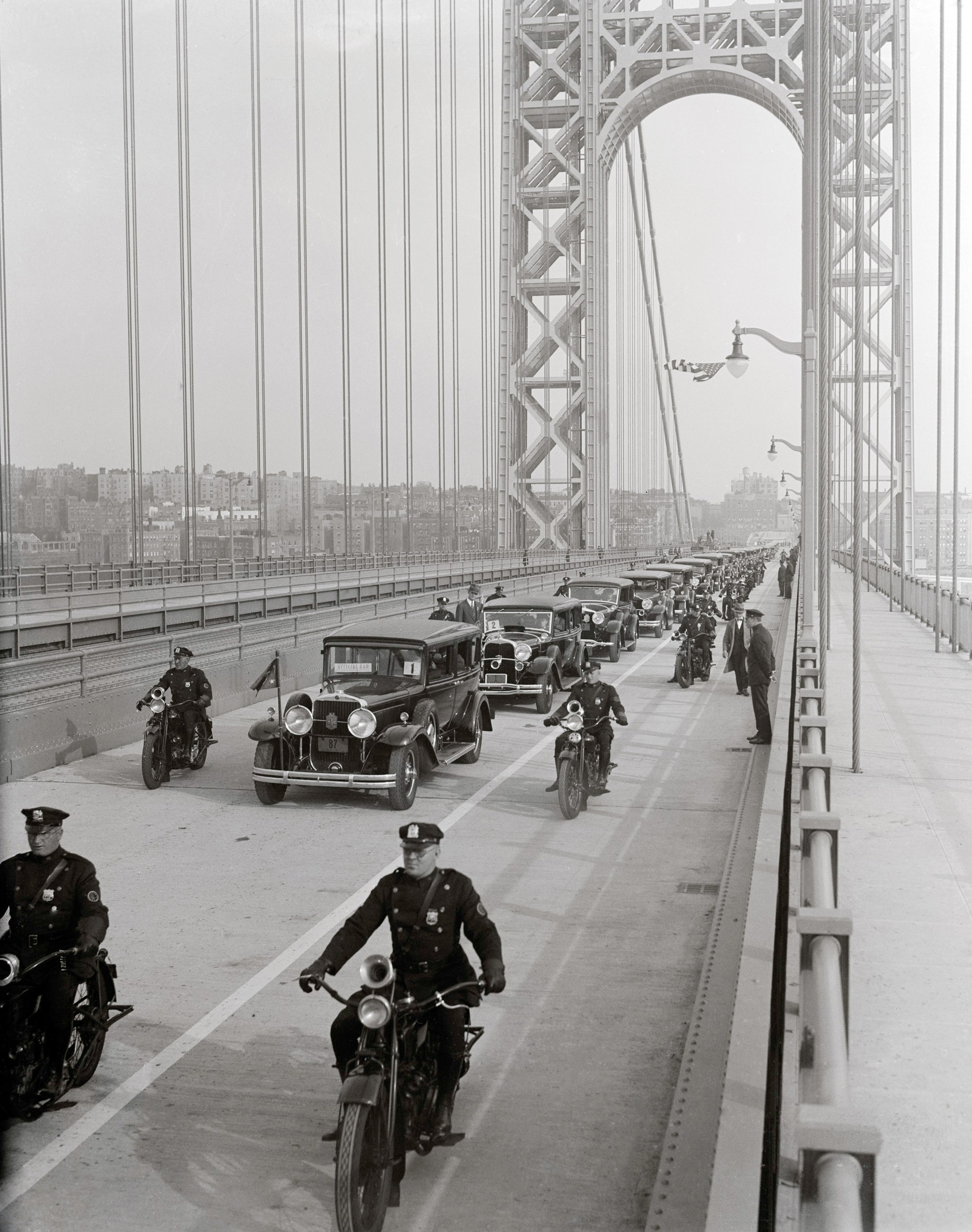 The New George Washington Memorial Bridge, a modern miracle, connecting New York with New Jersey, was opened, Oct. 24, 1931, with elaborate ceremonies in which Governor Roosevelt of New York, Governor Larson of New Jersey and Secretary of the Navy Adams participated. Here, official cars cross the huge span for the dedication ceremonies.