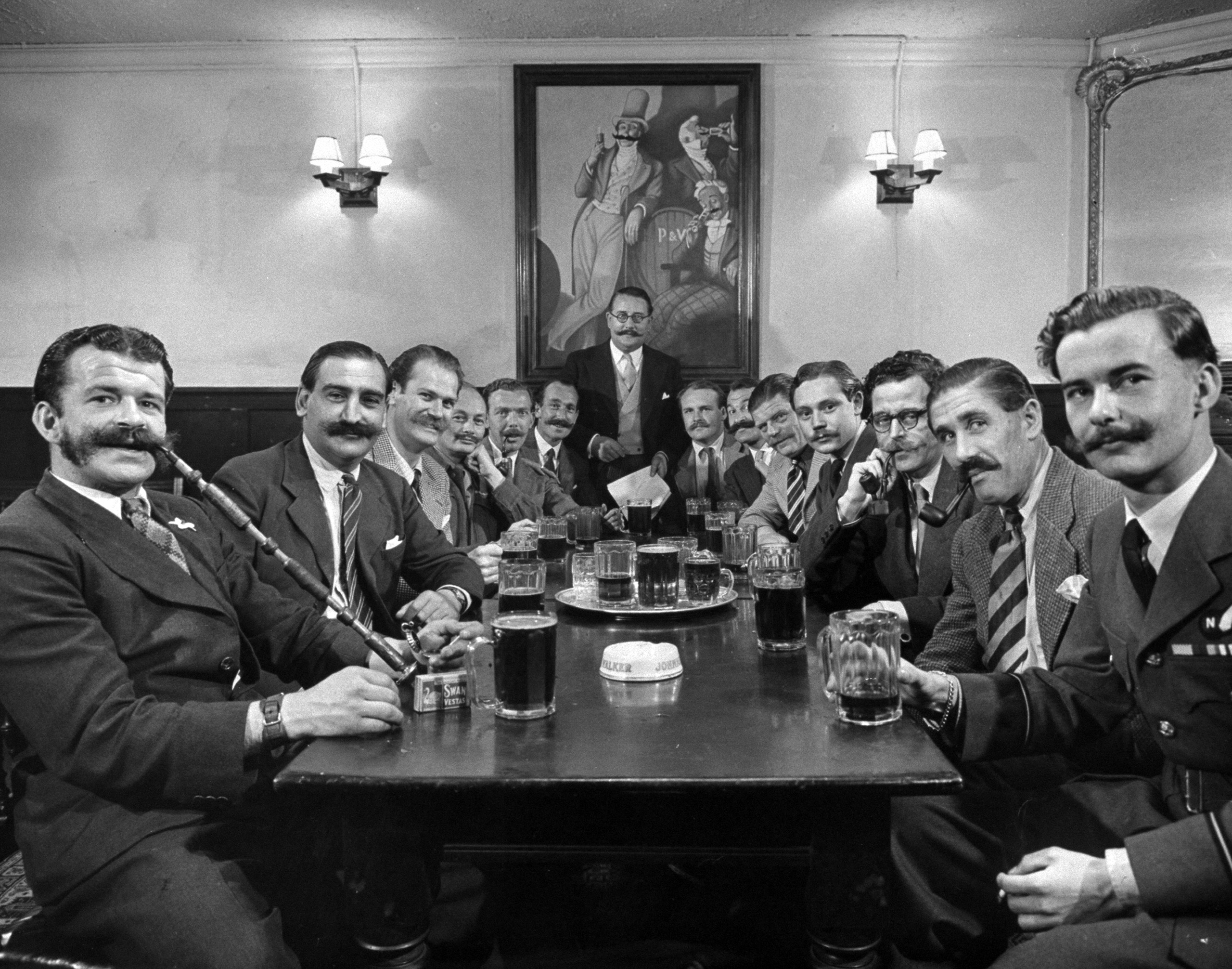 Caption from LIFE. At Temple Public House, club members hold formal beer session. The mustaches in the picture on their wall have been taped on.