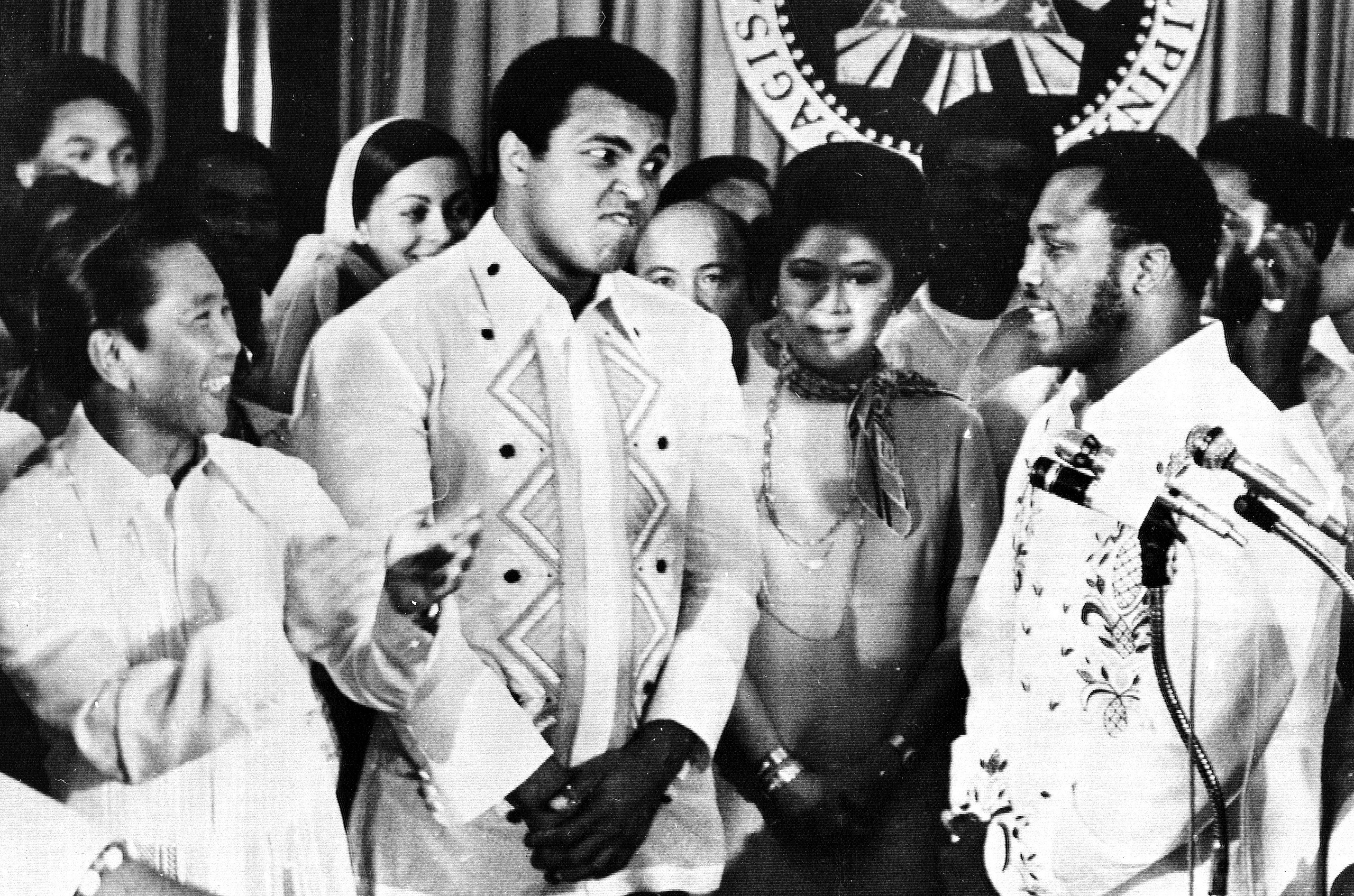 Philippines President Ferdinand Marcos, left, applauds as challenger Joe Frazier, right, makes some remarks about world champion Muhammad Ali, second from left, during their call on Marcos at the Malacanang Palace in Manila, on Sept. 18, 1975.  Between the two fighters is Marco's wife Imelda.