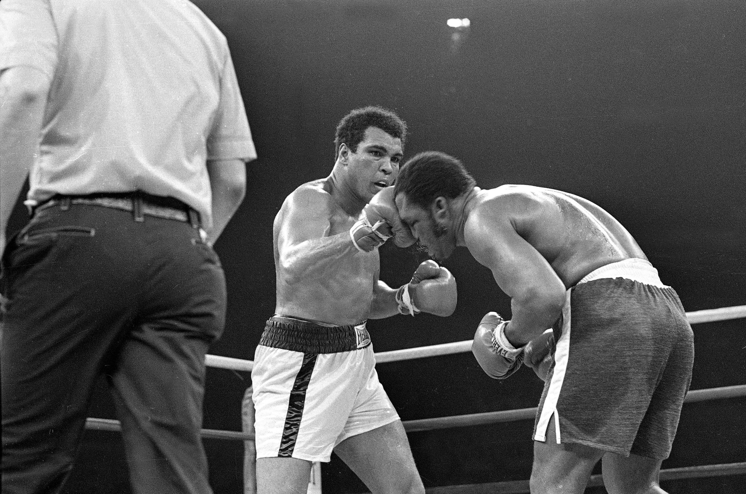 Muhammad Ali connects with the top of Joe Frazier's head in the 13th round of their bout for the heavyweight title at Araneta Coliseum in Manila, Oct. 1, 1975.