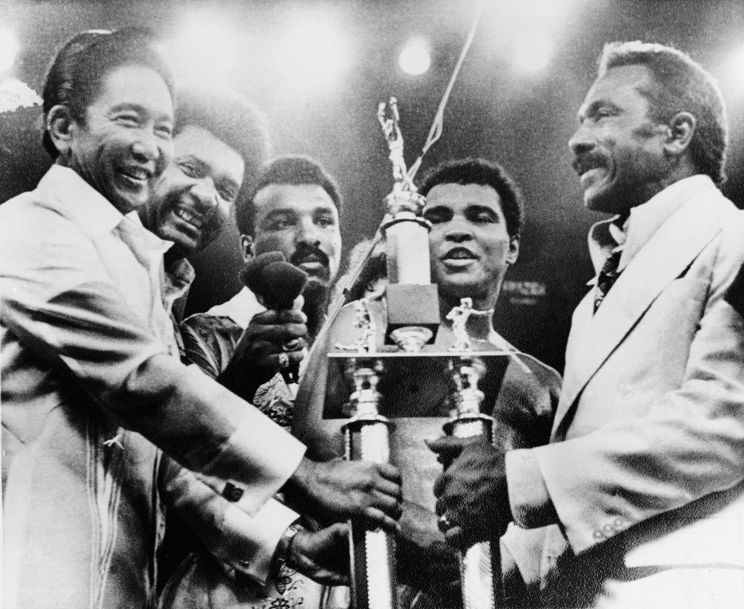 President Ferdinand Marcos, left, of the Philippines, presents the President's Trophy to heavyweight champion Muhammad Ali, second from right, after Ali defeated Joe Frazier in their  Thrilla in Manila  fight at the Coliseum in Manila, Oct. 1, 1975.  Posing from left are, President Marcos; promoter Don King; Ali's brother, Rahman; Ali, and his father Cassius Marcellus Clay Sr., right.