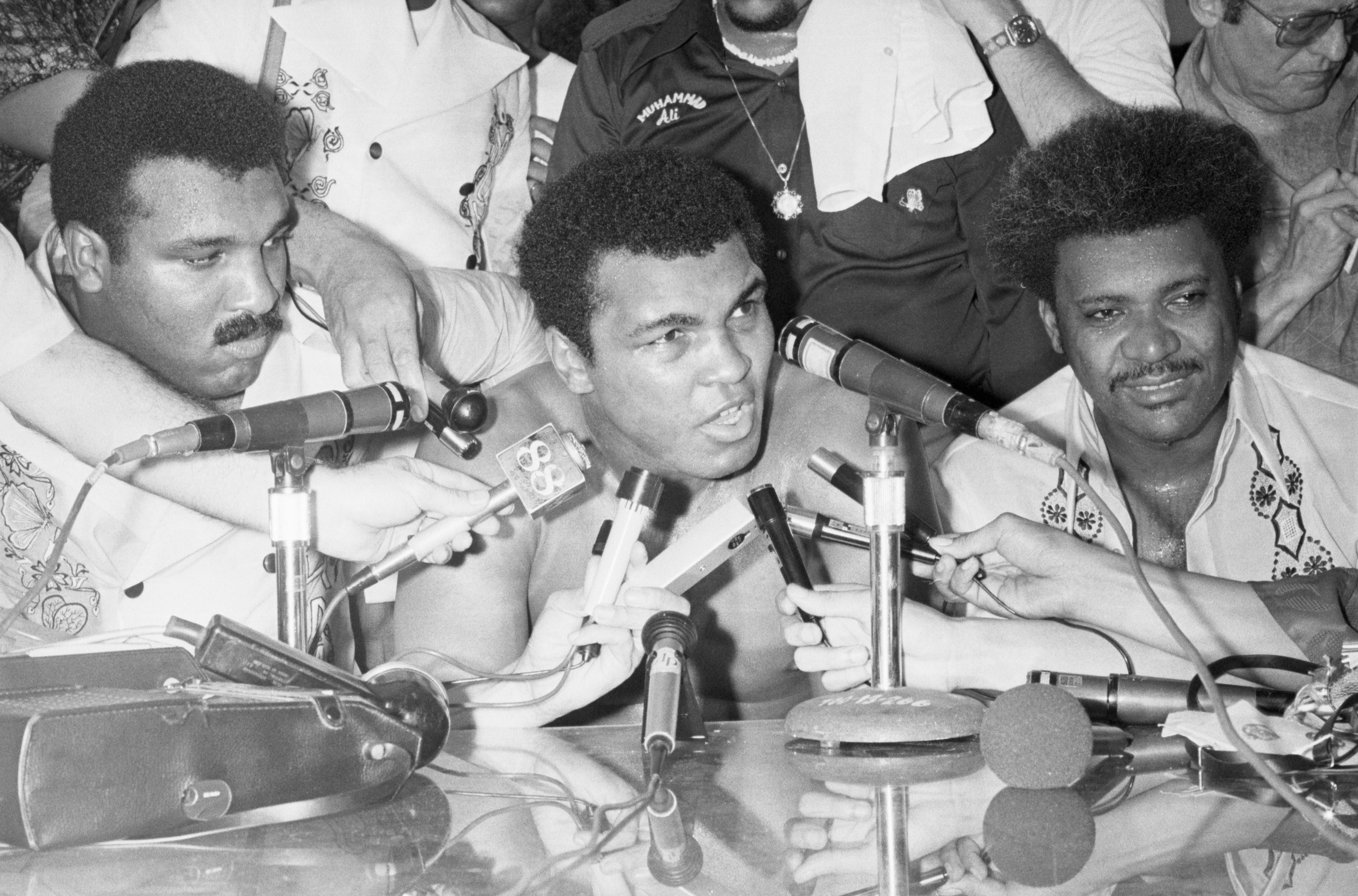 Heavyweight champion of the world Muhammad Ali (C) meets with the press after defeating challenger Smokin' Joe Frazier in the 14th round by TKO. Next to Ali is boxing promoter Don King (R), and Ali's brother Rahaman. Manila, Oct. 1, 1975.