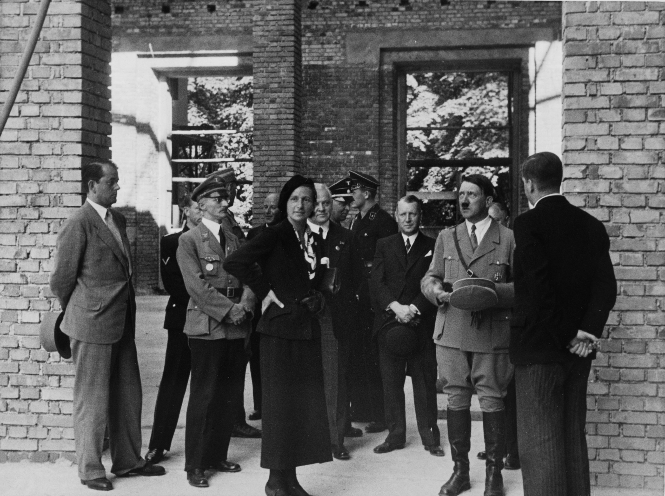 Heinrich Hoffmann photograph of architect Albert  Speer (far left), interior designer Gerdy Troost, Hitler, and others inspecting the House of German Art construction site in Munich on June 29, 1935, on the occasion of the topping-out ceremony.