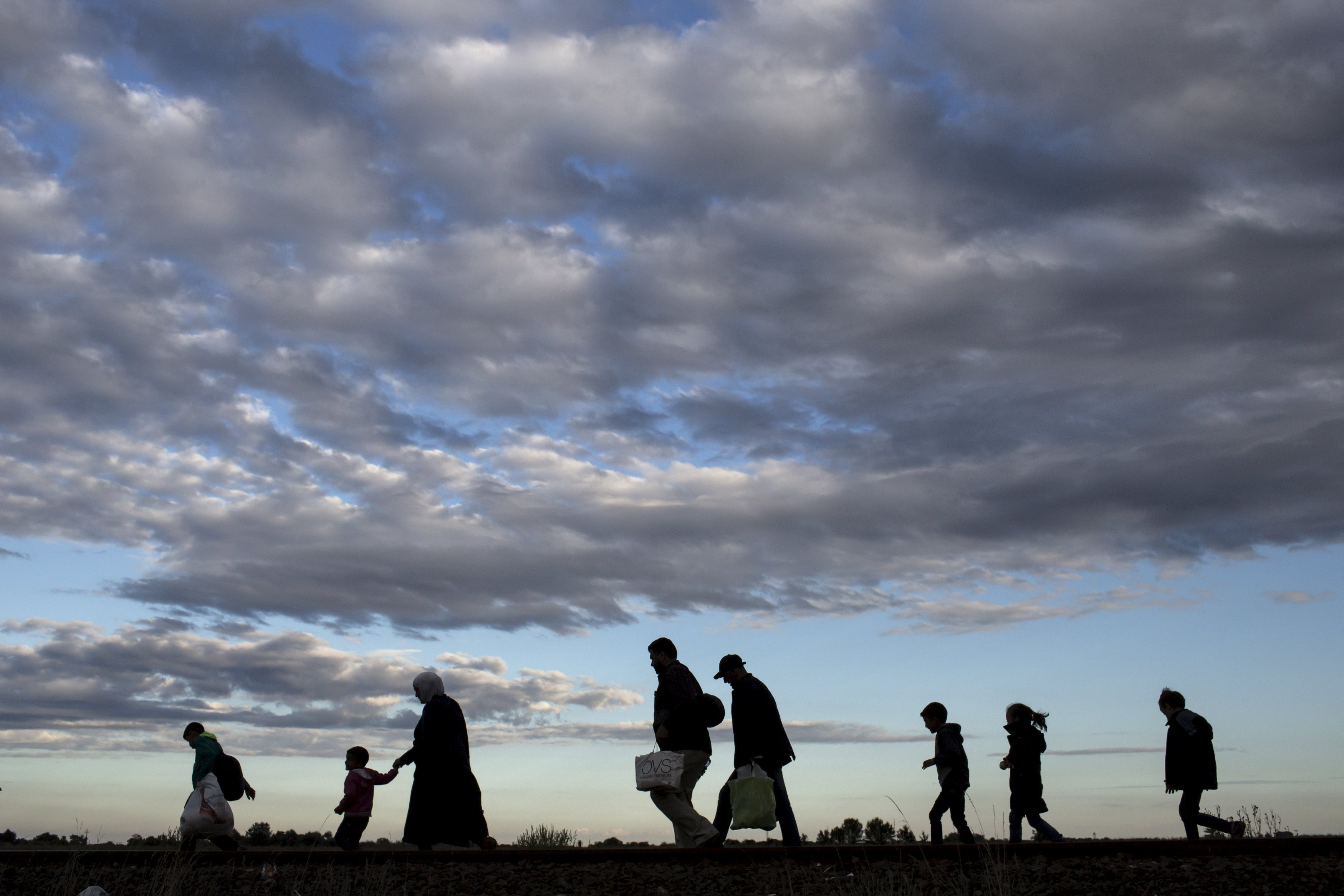 Migrants walk along rail tracks as they arrive to a collection point in the village of Roszke, Hungary, on Sept. 6, 2015.