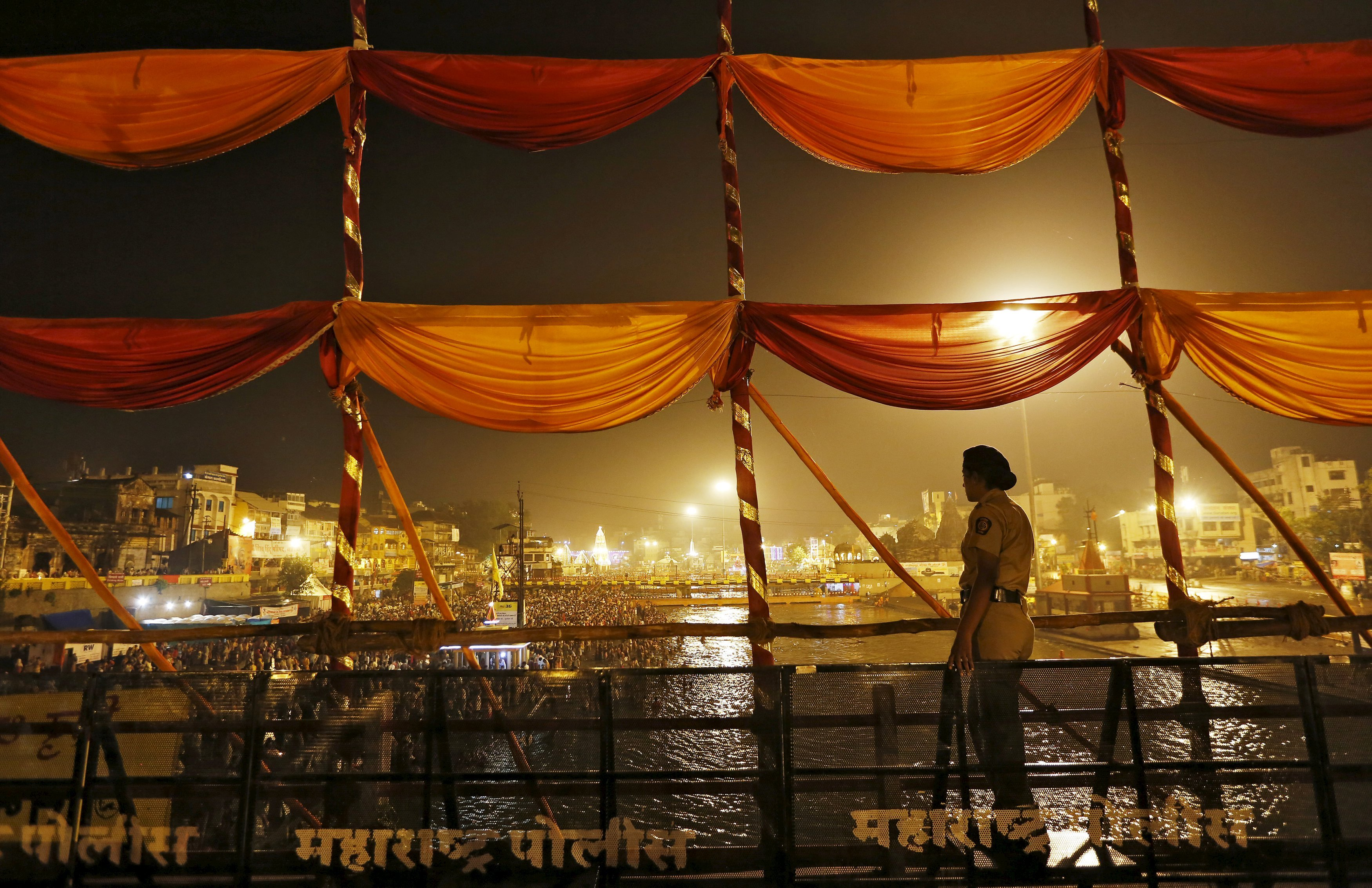 """A policewoman stands guard as Hindu devotees take a dip in the waters of Godavari river during the second """"Shahi Snanâ€ù (grand bath) at Kumbh Mela in Nashik, India, on Sept. 13, 2015."""