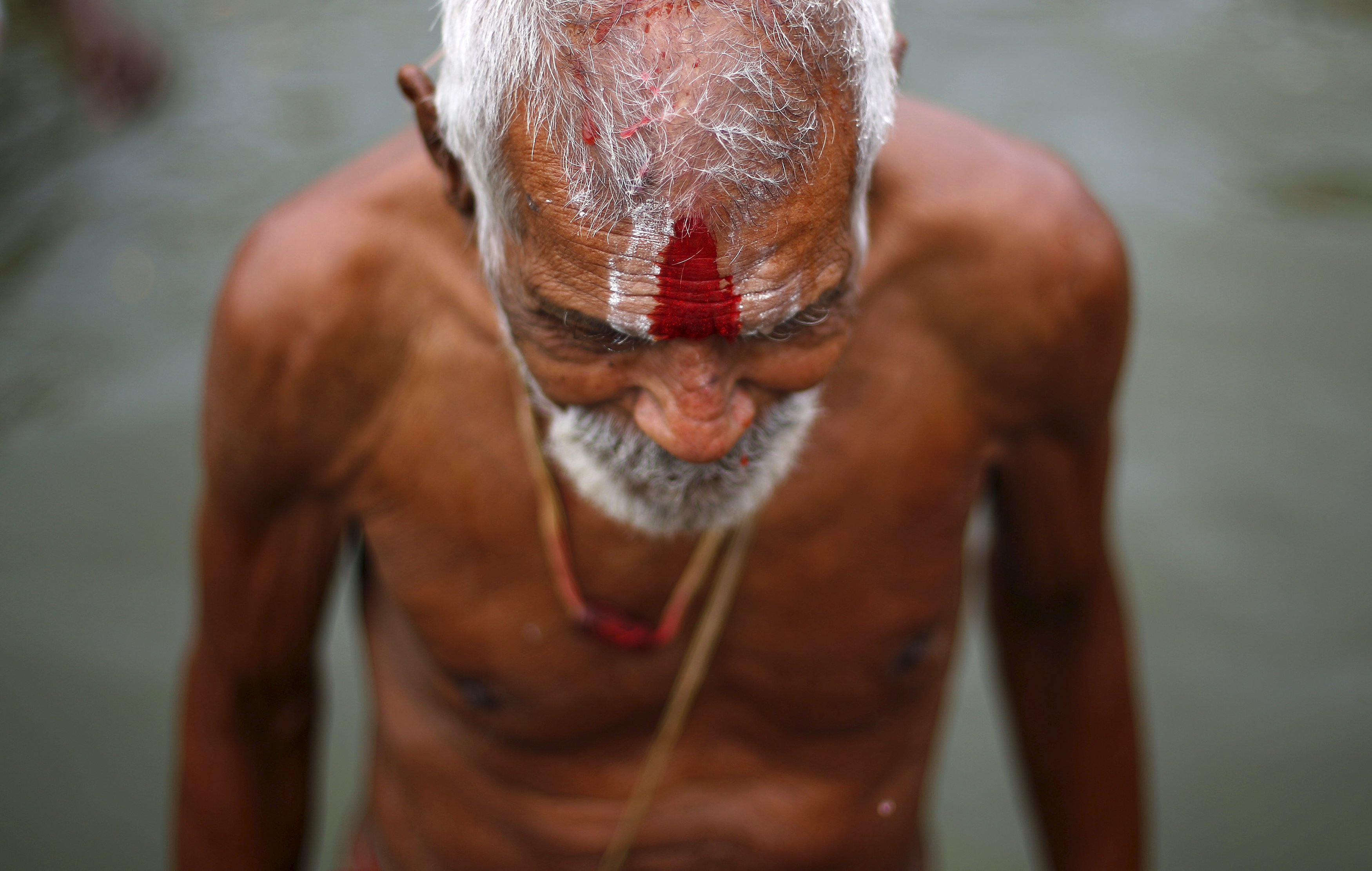 """A sadhu or a Hindu holy man comes out of the waters of Godavari river after taking a dip during the second """"Shahi Snanâ€ù (grand bath) at Kumbh Mela in Nashik, India, on Sept. 13, 2015."""