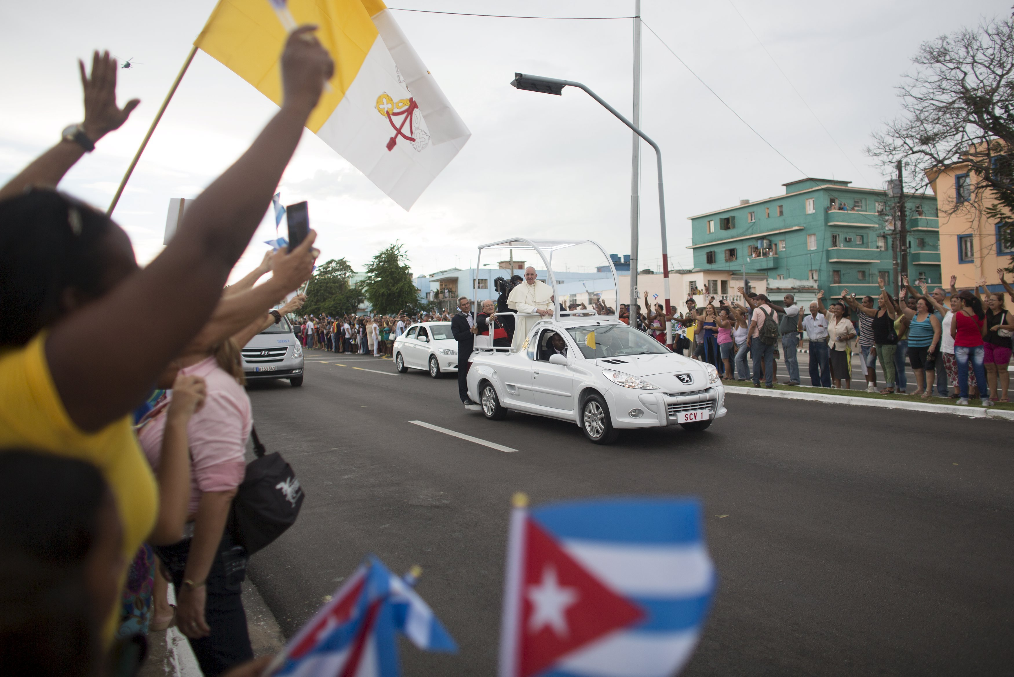 People react as Pope Francis arrives at the airport in Havana, Sept. 19, 2015.