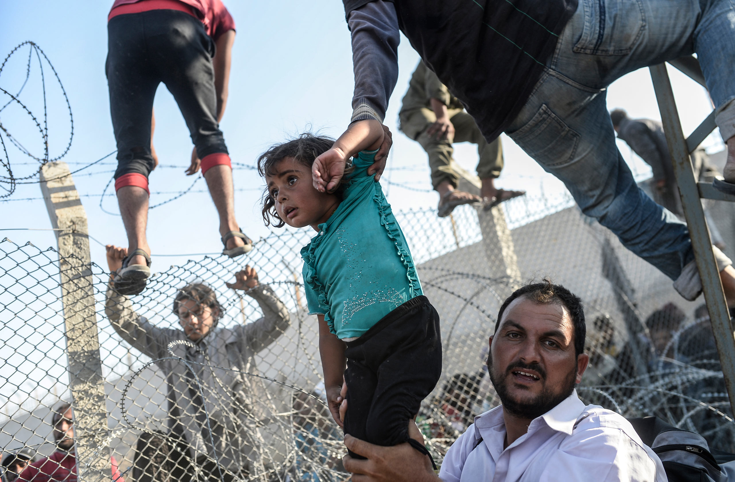 Thousands of Syrians break through the fences, crossing illegally the Syrian-Turkish border. Many of them are little children and infants. June 14, 2015.