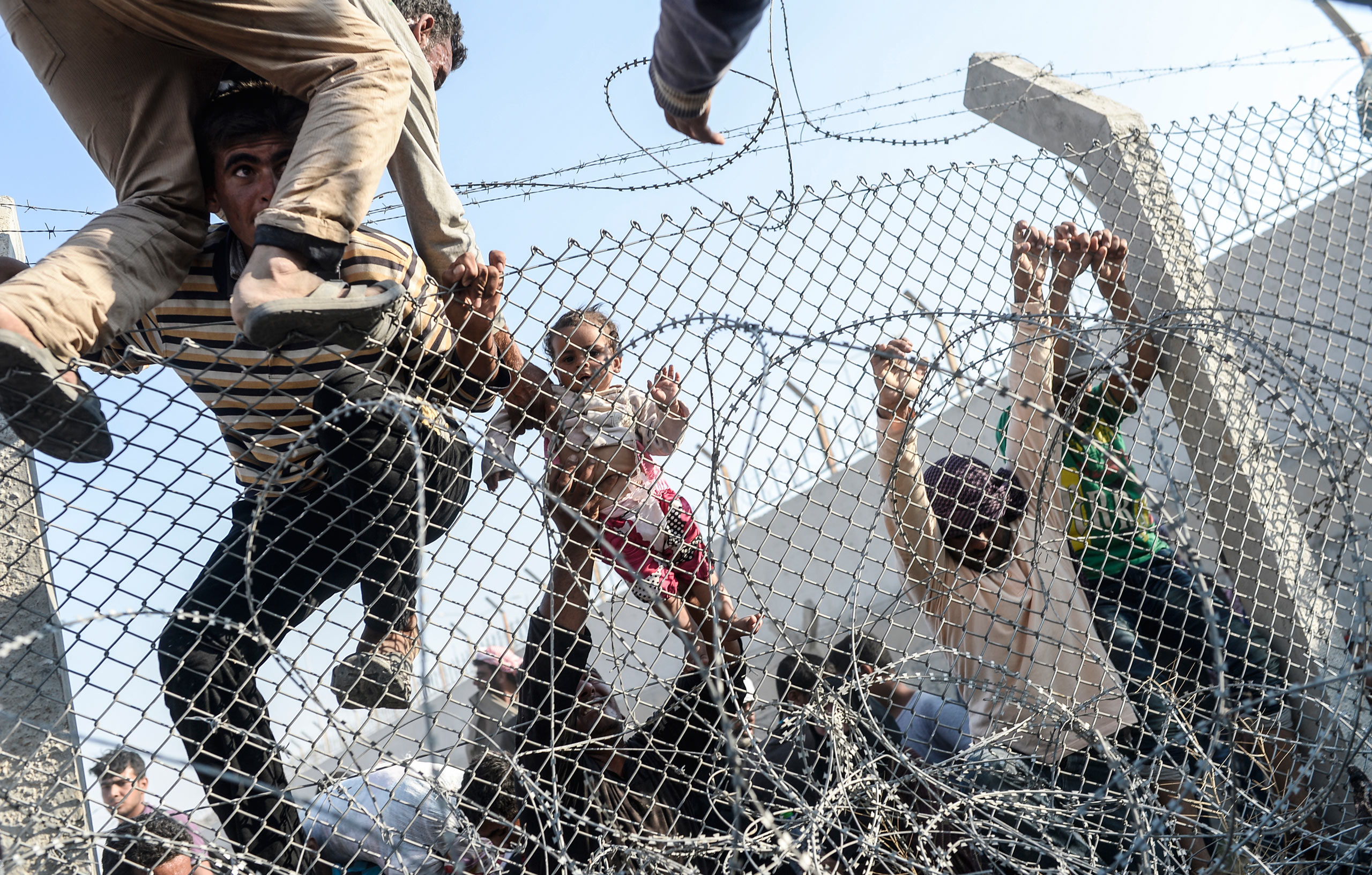 Syrian refugees break through the wire fences, crossing illegally the Syrian-Turkish border.  June 14, 2015.