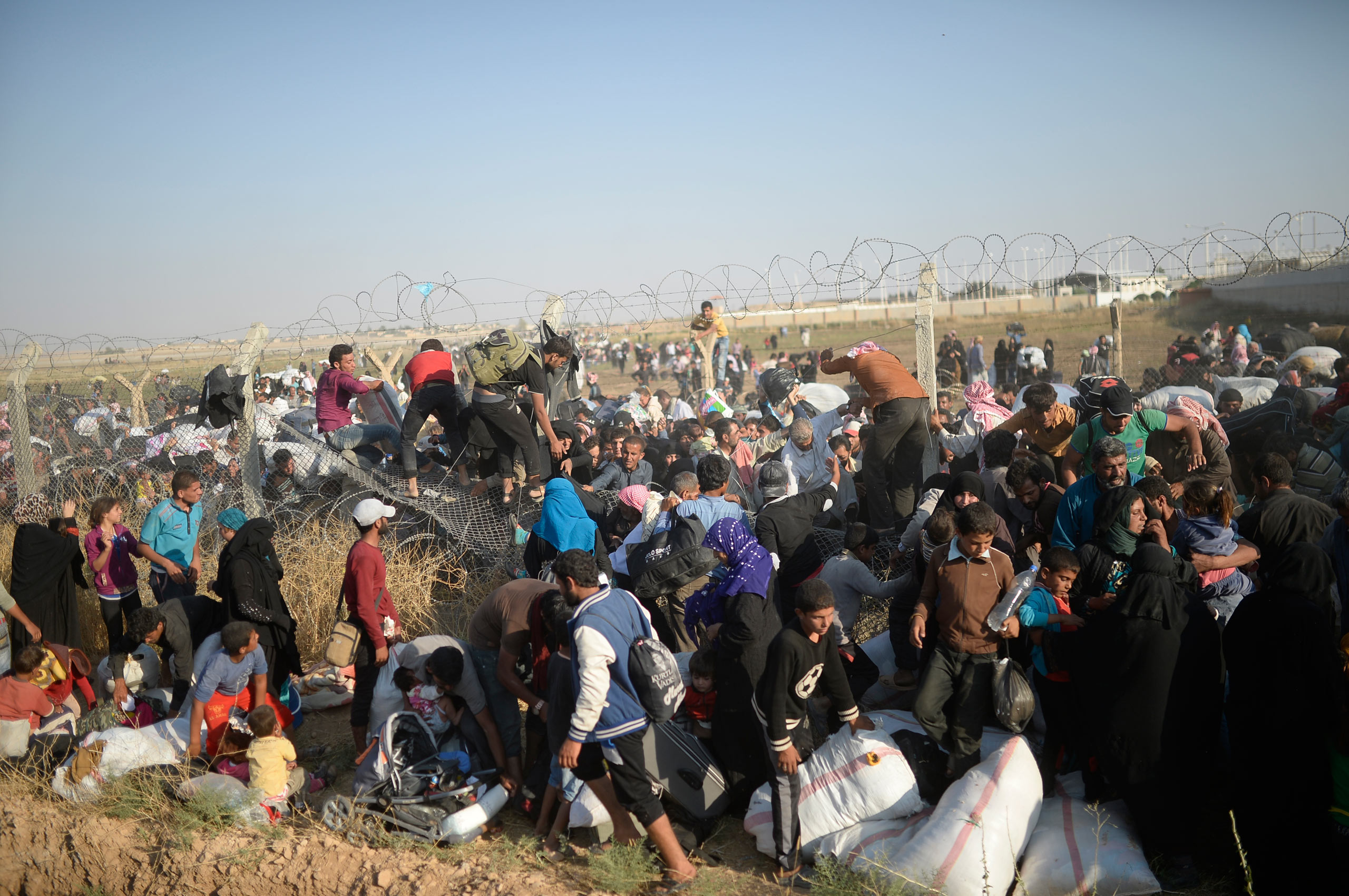 Thousands of Syrians break through the ripped fences, crossing illegally from the Syrian town of Tell Abyad into the Turkish crossing gate in Akçakale, in the Şanlıurfa province. June 14, 2015.