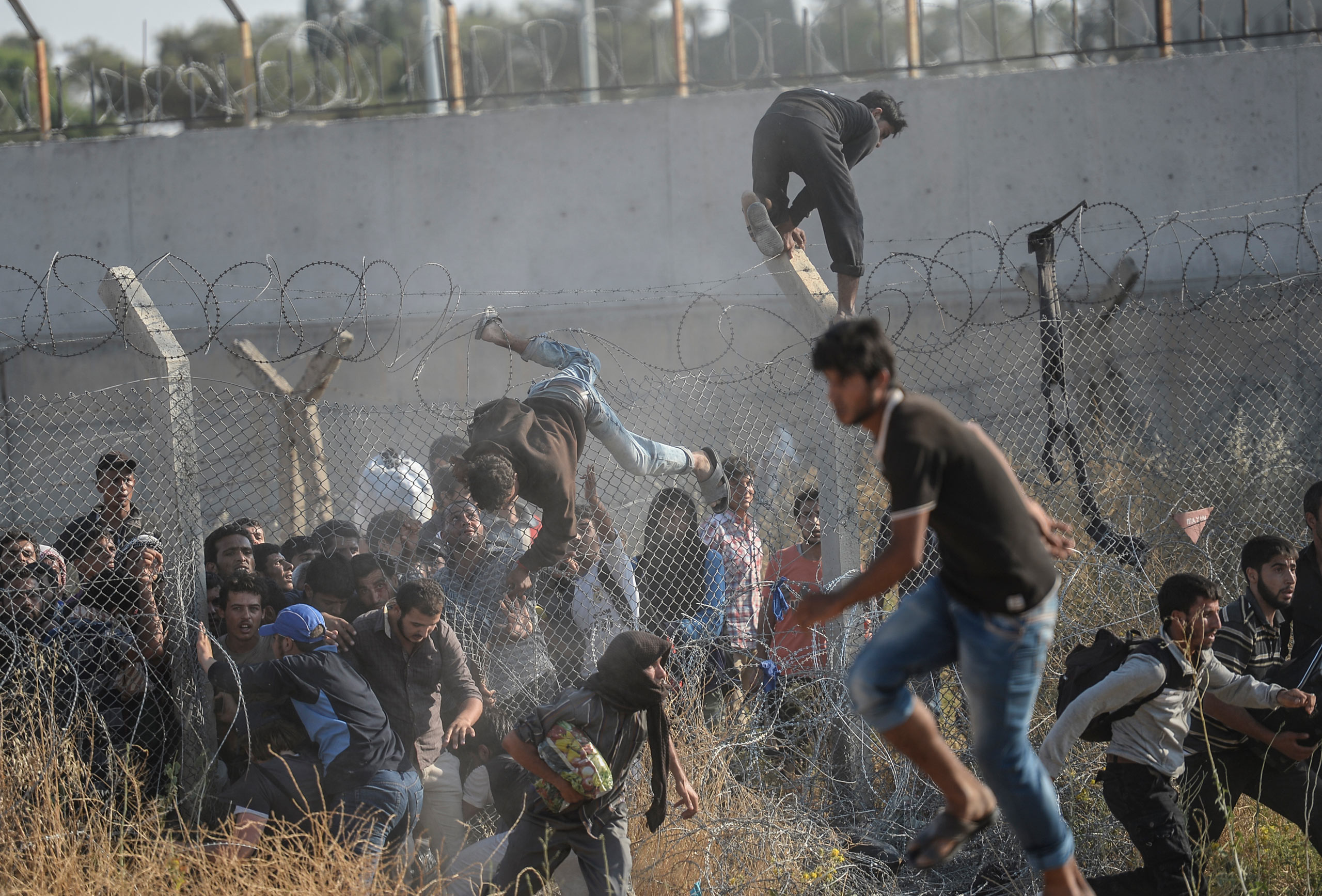 Thousands of Syrian refugees break down the wired fences, crossing illegally from the border city of Tell Abyad, as they heard that Kurdish fighters are approaching the Turkish crossing gate in Akçakale, in the Şanlıurfa province. June 14, 2015.