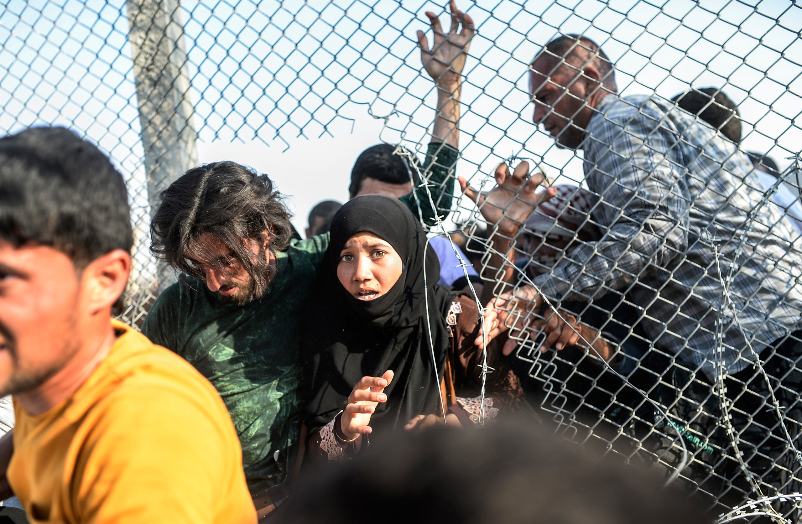 Thousands of Syrians break through the torn wired fences, crossing illegally from Tell Abyad into the Turkish territory in Akçakale, in the Şanlıurfa province. June 14, 2015.
