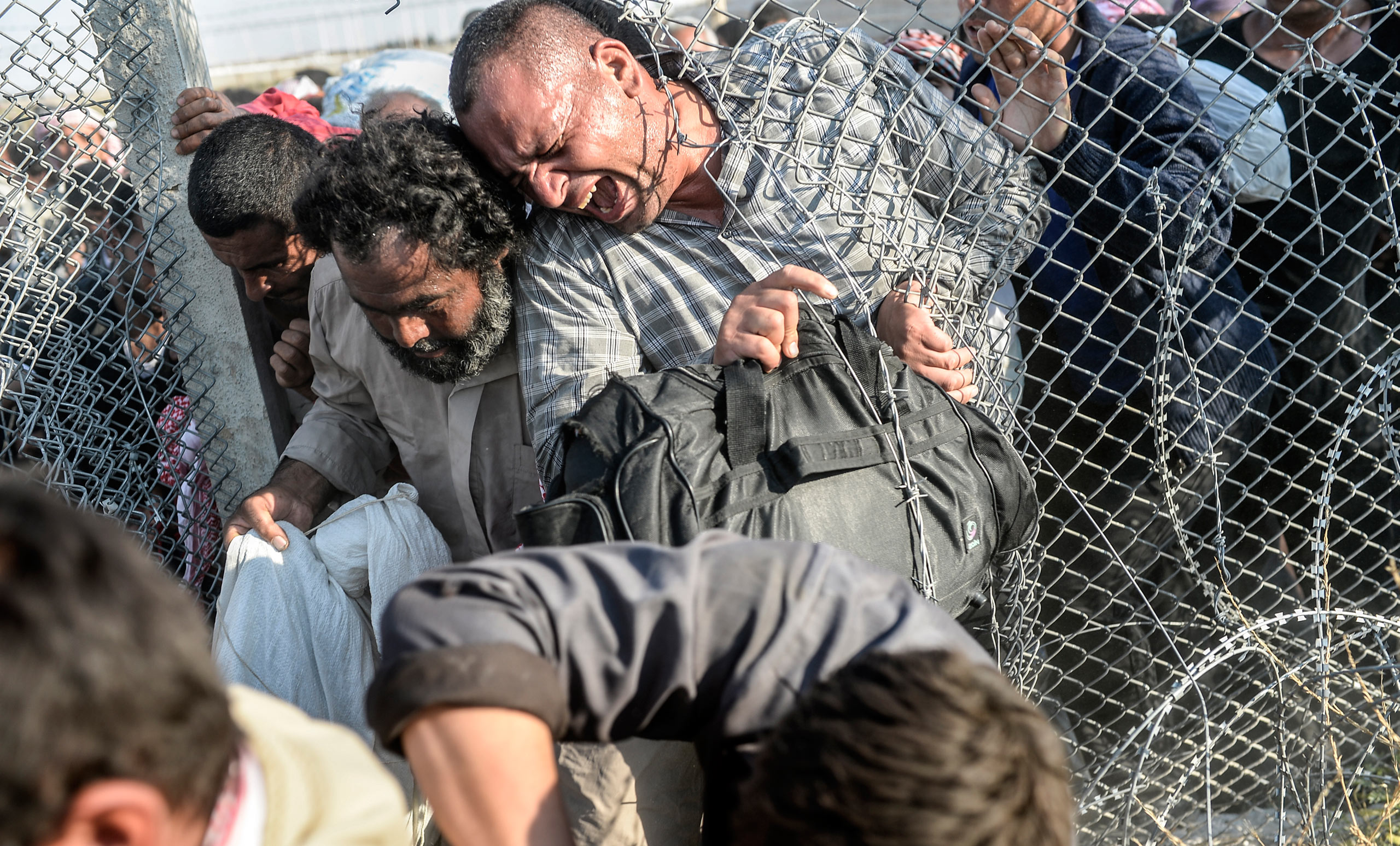 Thousands of Syrians break through the torn wire fences, crossing illegally from Tell Abyad into the Turkish territory in Akçakale, in the Şanlıurfa province. June 14, 2015.