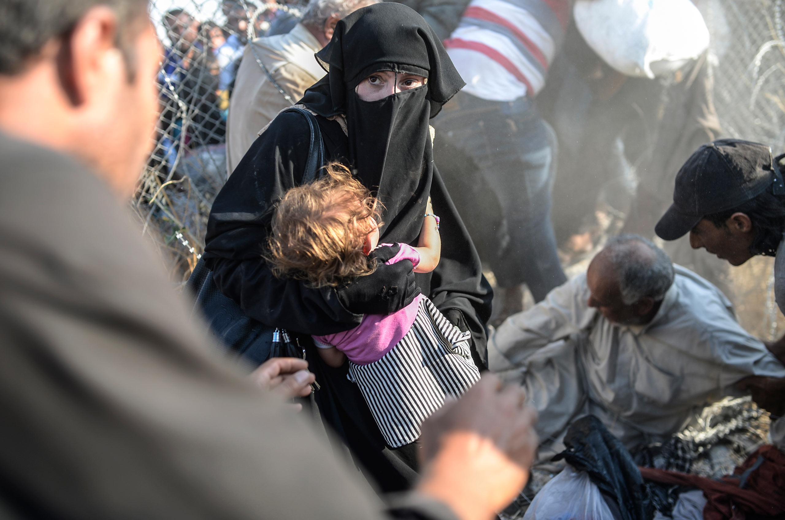 A Syrian woman holds her child as they pass the wire fence at the Turkish border near the Syrian town of Tell Abyad and Akçakale, in the Şanlıurfa province. June 14, 2015.