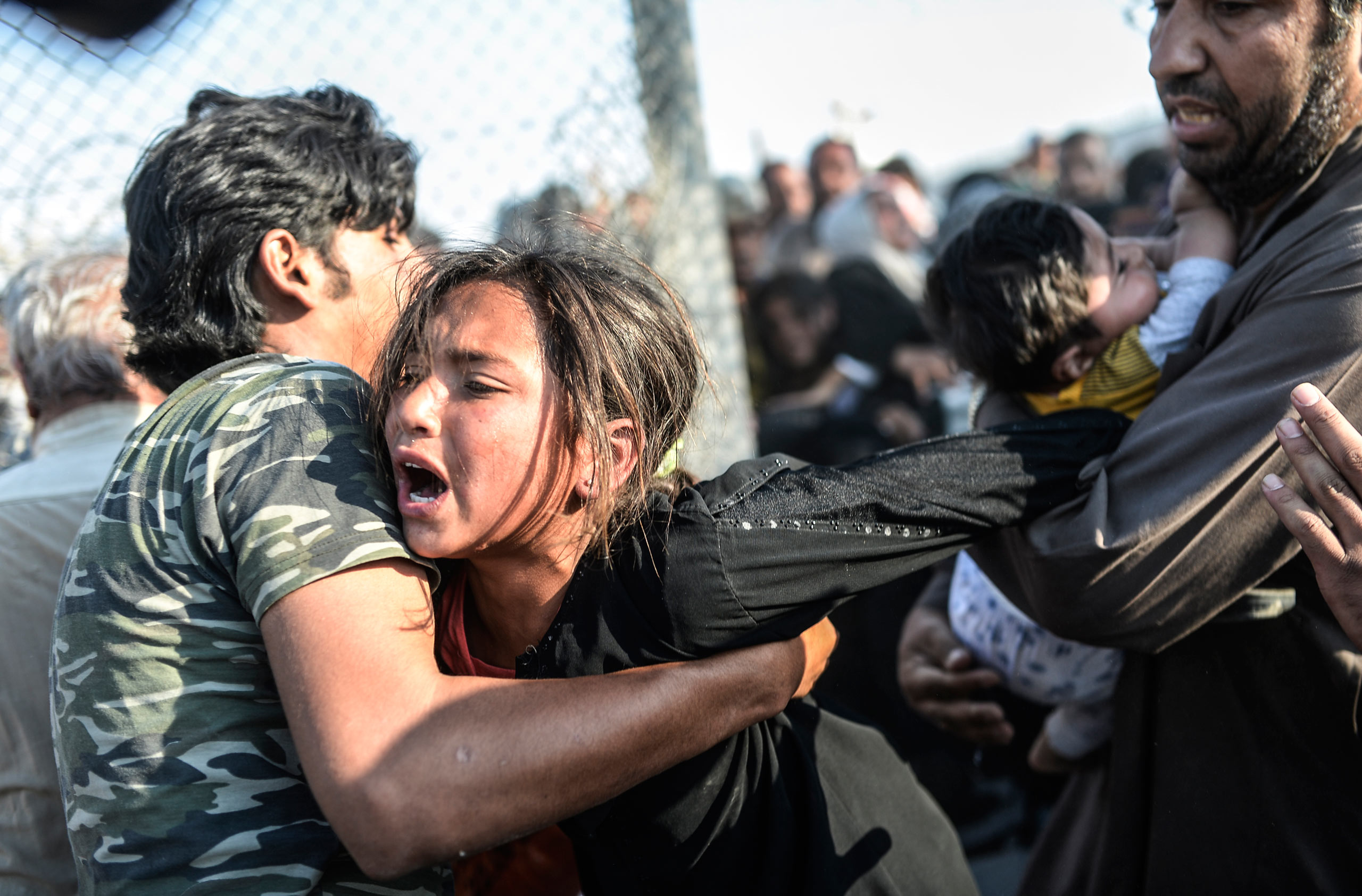 Thousands of Syrians break through the wired ripped fences, crossing illegally from the Syrian town of Tell Abyad to Akçakale, in the Şanlıurfa province. June 14, 2015.