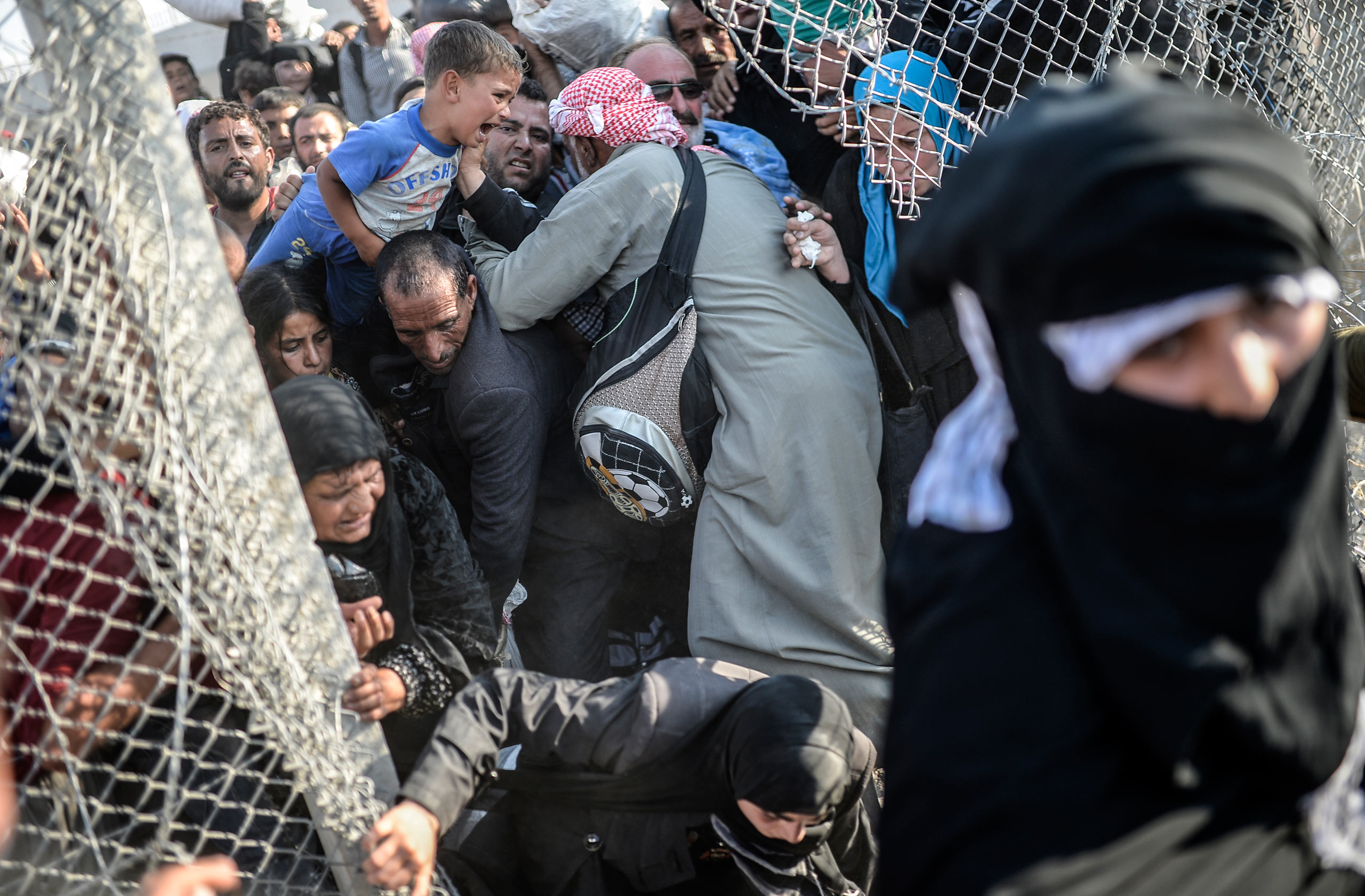 Thousands of Syrians break through the wired ripped fences, crossing from the Syrian town of Tell Abyad into Akçakale, in the Şanlıurfa province. June 14, 2015.