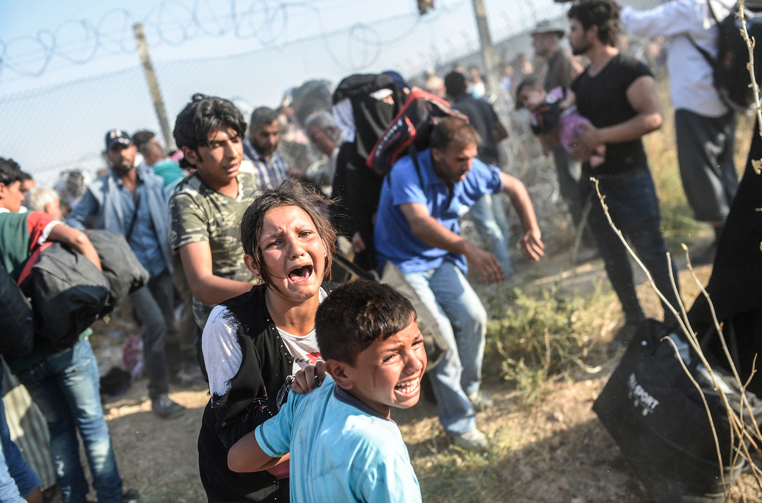 Thousands of Syrians break through the ripped fences, crossing from the Syrian town of Tell Abyad into Akçakale, in the Şanlıurfa province. Many of the refugees are families with little children and infants. June 14, 2015.
