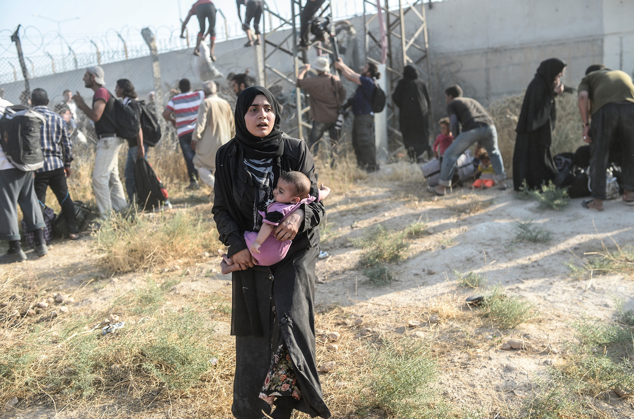 A woman carries her baby near the fences at the crossing gate between the Syrian town of Tell Abyad and Akçakale, in the Turkish Şanlıurfa province.  June 14, 2015.