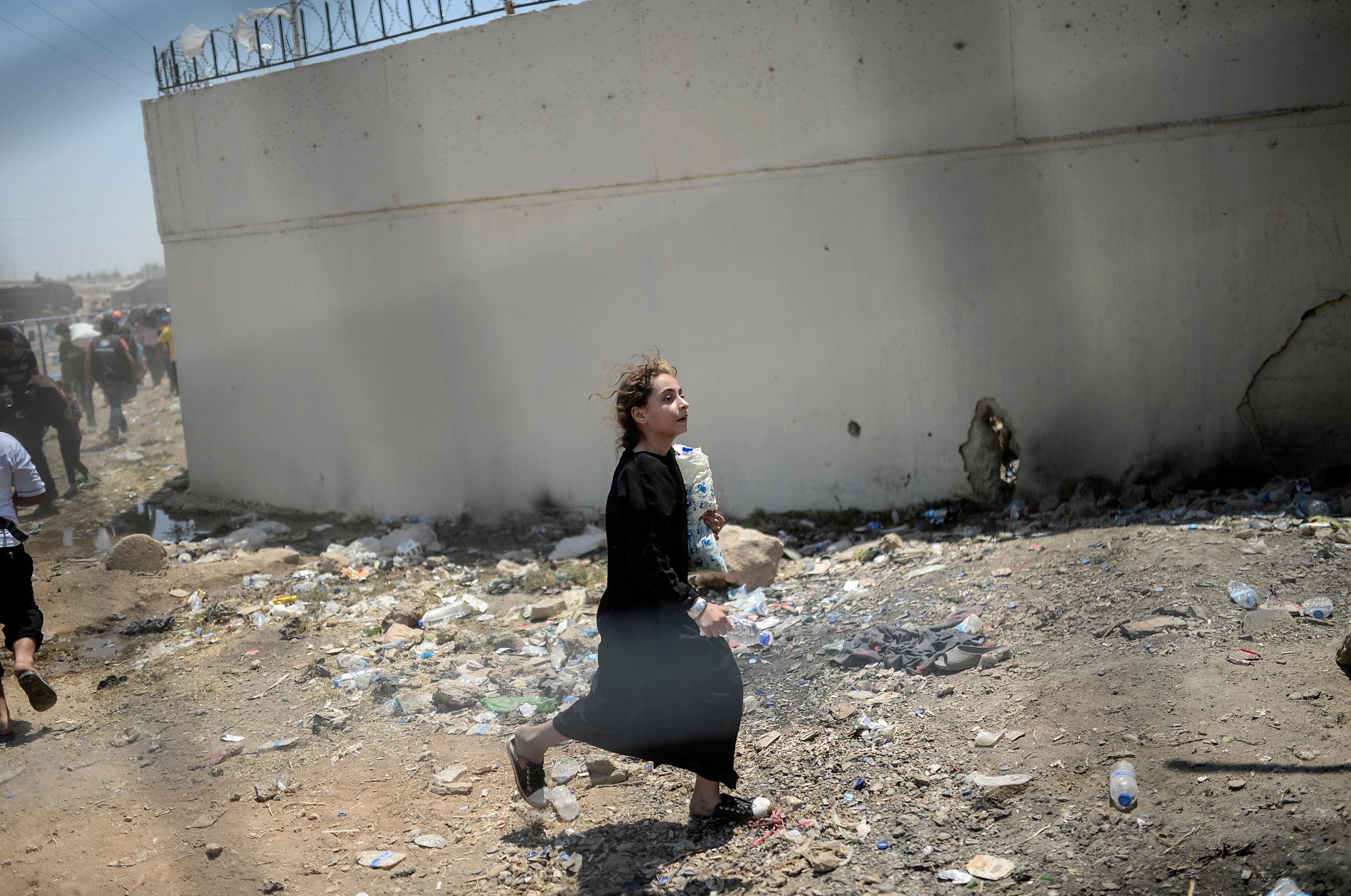 A Syrian woman walks through the crossing gate in Akçakale, in the Şanlıurfa province of Turkey. June 15, 2015.