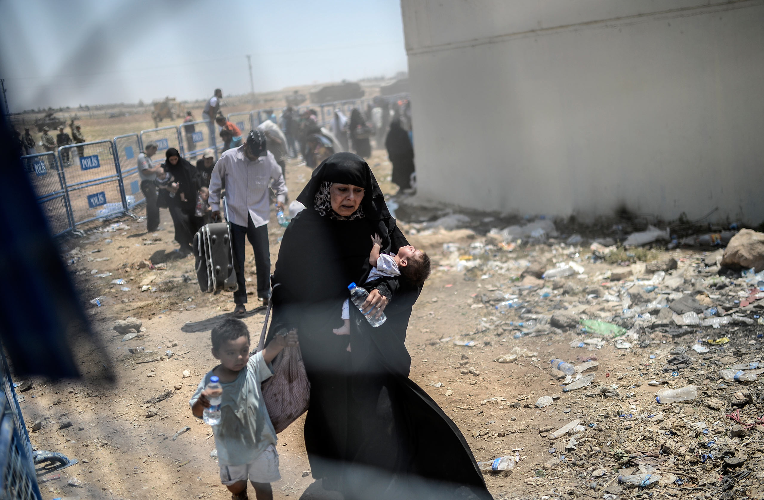 A Syrian woman fleeing her war-torn country with her children enters Turkey through the Turkish crossing gate in Akçakale, in the Şanlıurfa province. June 15, 2015.