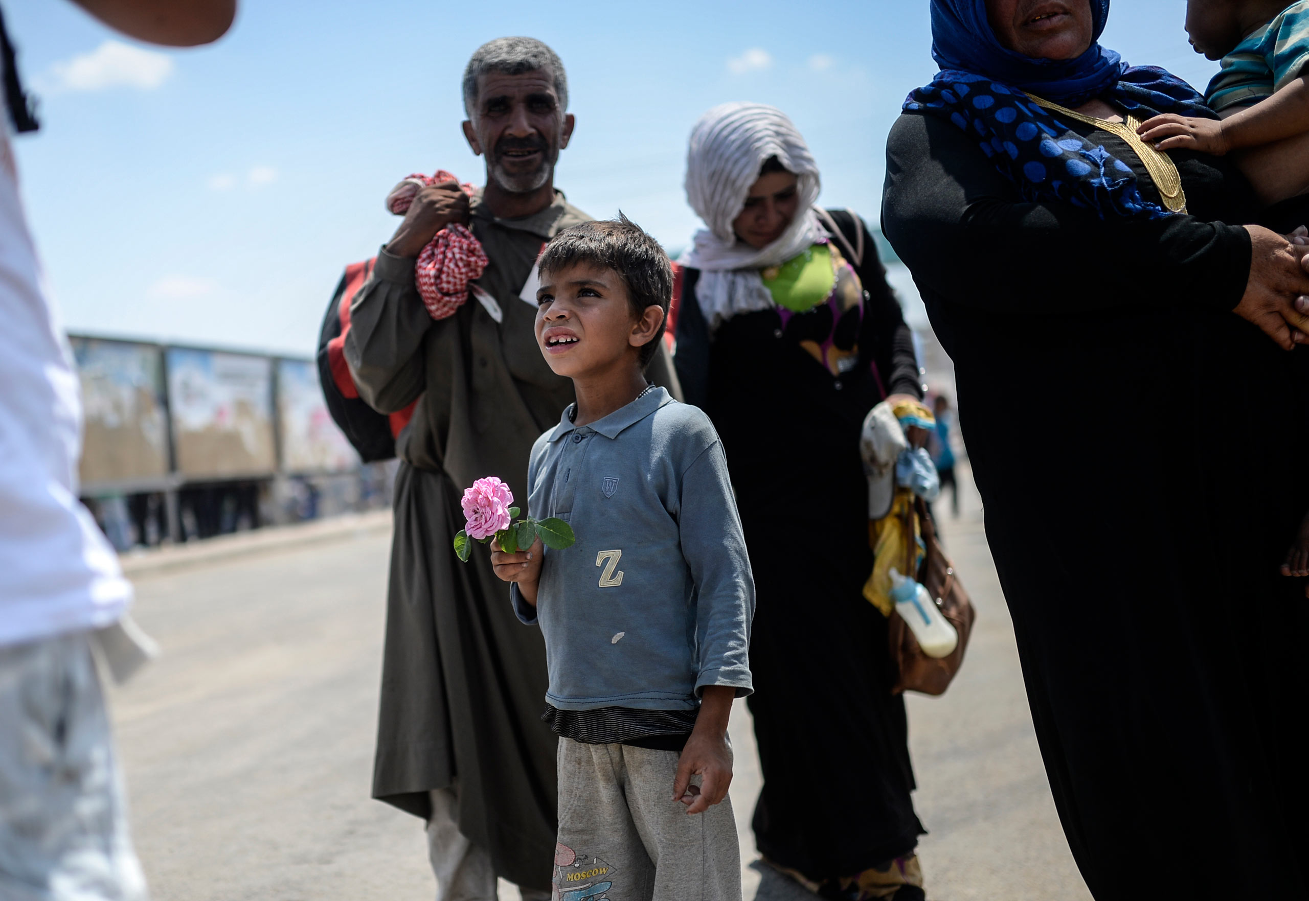 A Syrian boy holds a rose after he arrives at Turkey through the Turkish crossing gate in Akçakale, in the Şanlıurfa province. June 15, 2015.