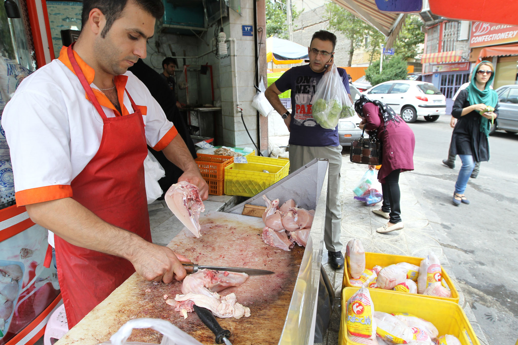 An Iranian man buys fresh chicken at a poultry shop in Tehran on July 24, 2012.