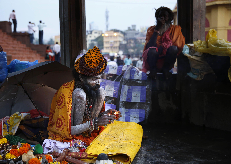 A Naga sadhu, or naked Hindu holy man, smokes hashish on the banks of the Godavari River during Kumbh Mela in Nasik, India, on Sept. 12, 2015.