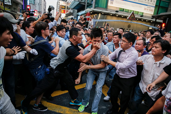 Hong Kong youth protesting against the Chinese government,  an angry crowd, mostly shopkeepers  who can not work and people paid by triads attacked a pro-democracy camp students in October 3, 2014 in Hong Kong