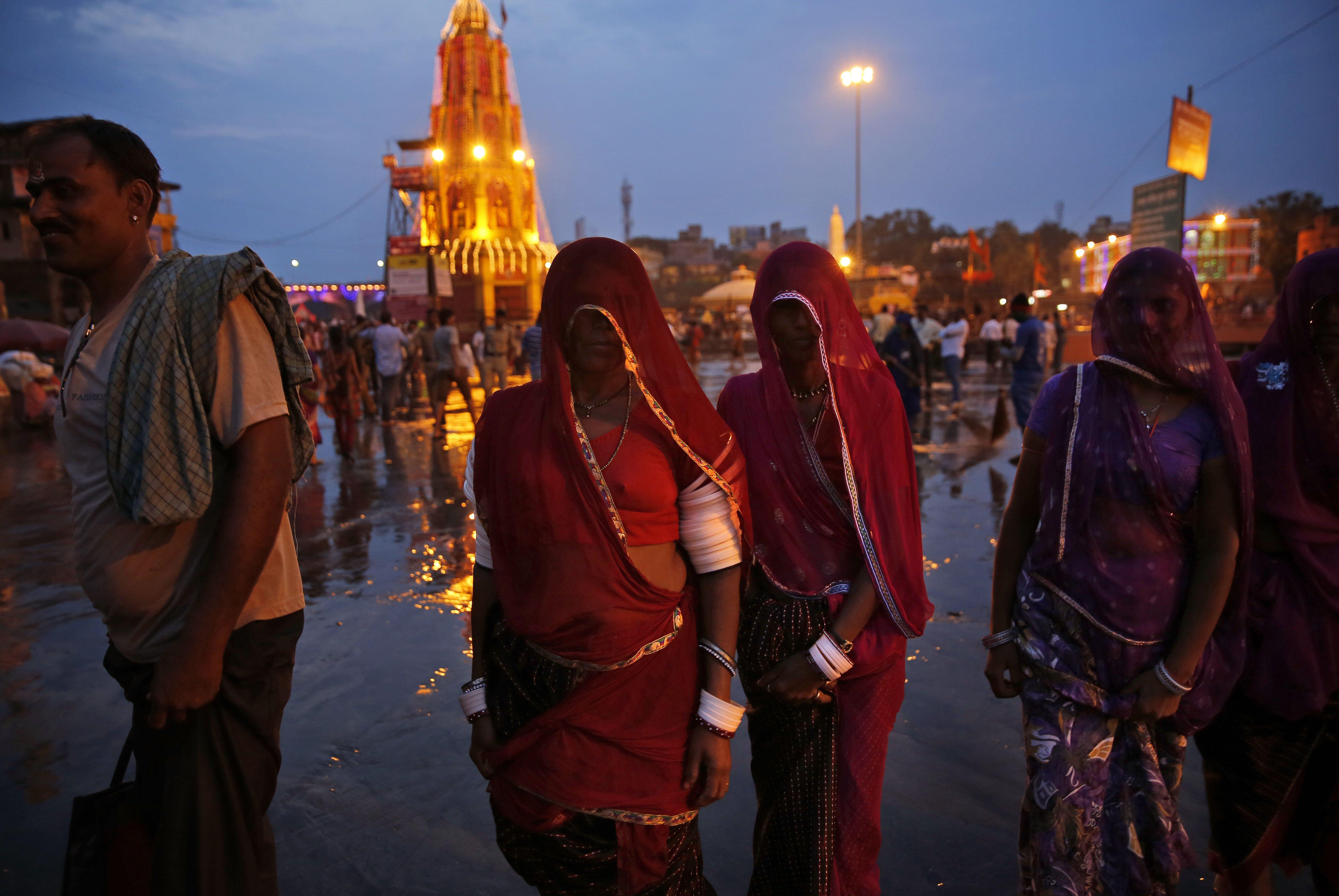 Indian women devotees arrive on the banks of the Godavari River for the second royal bath during Kumbh Mela, or Pitcher Festival in Nasik, India, on Sept. 12, 2015.