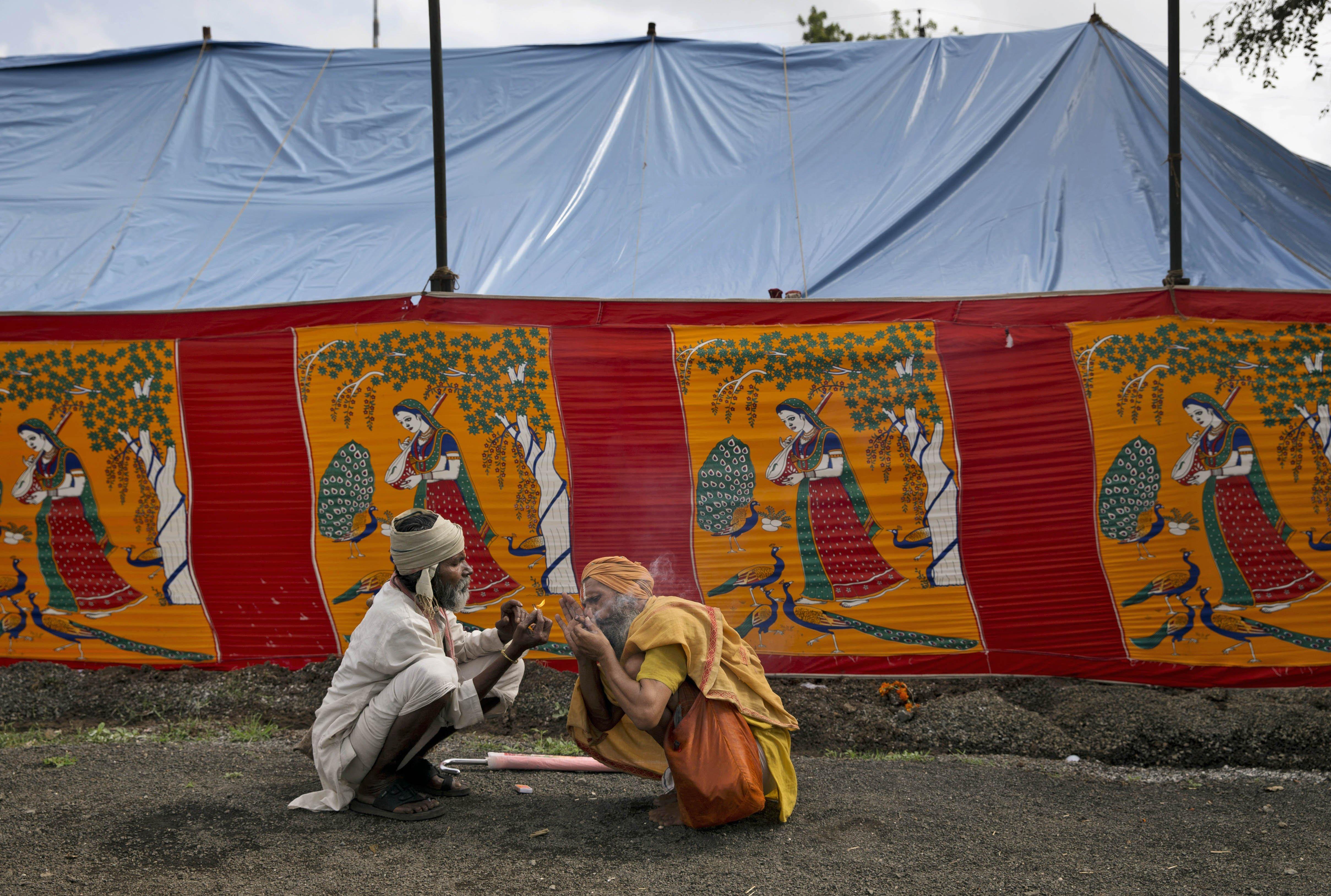 Indian Sadhus, or Hindu holy men, smoke near a makeshift shelter at the Kumbh Mela in Nasik, India, on Aug. 27, 2015.