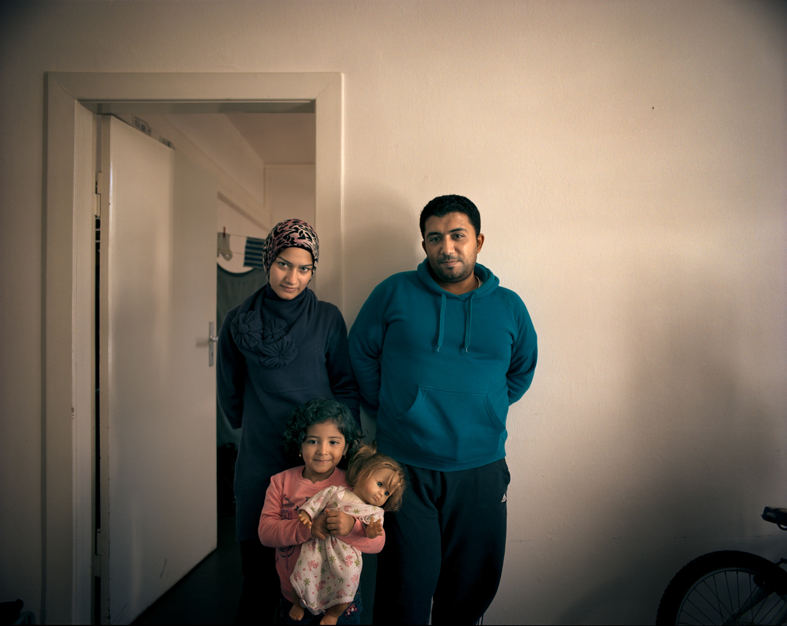 "Hasan Maaz, 32, owned a small shop in Aleppo selling cell phones, with his wife Nahed Sikkarit, 24,  a former hairdresser. They would eventually like to work in Germany—but they are still awaiting their papers, living in the Wilmersdorf refugee shelter in Berlin.                                                               In the meantime, they are just grateful to have found sanctuary. ""We thank Allah that we are finished with the rockets and bombs and are safe,"" says Maaz. Their daughter Mayyar Alhelwa has something to smile about too: after losing her first doll on the boat to Greece, she now has a new one."