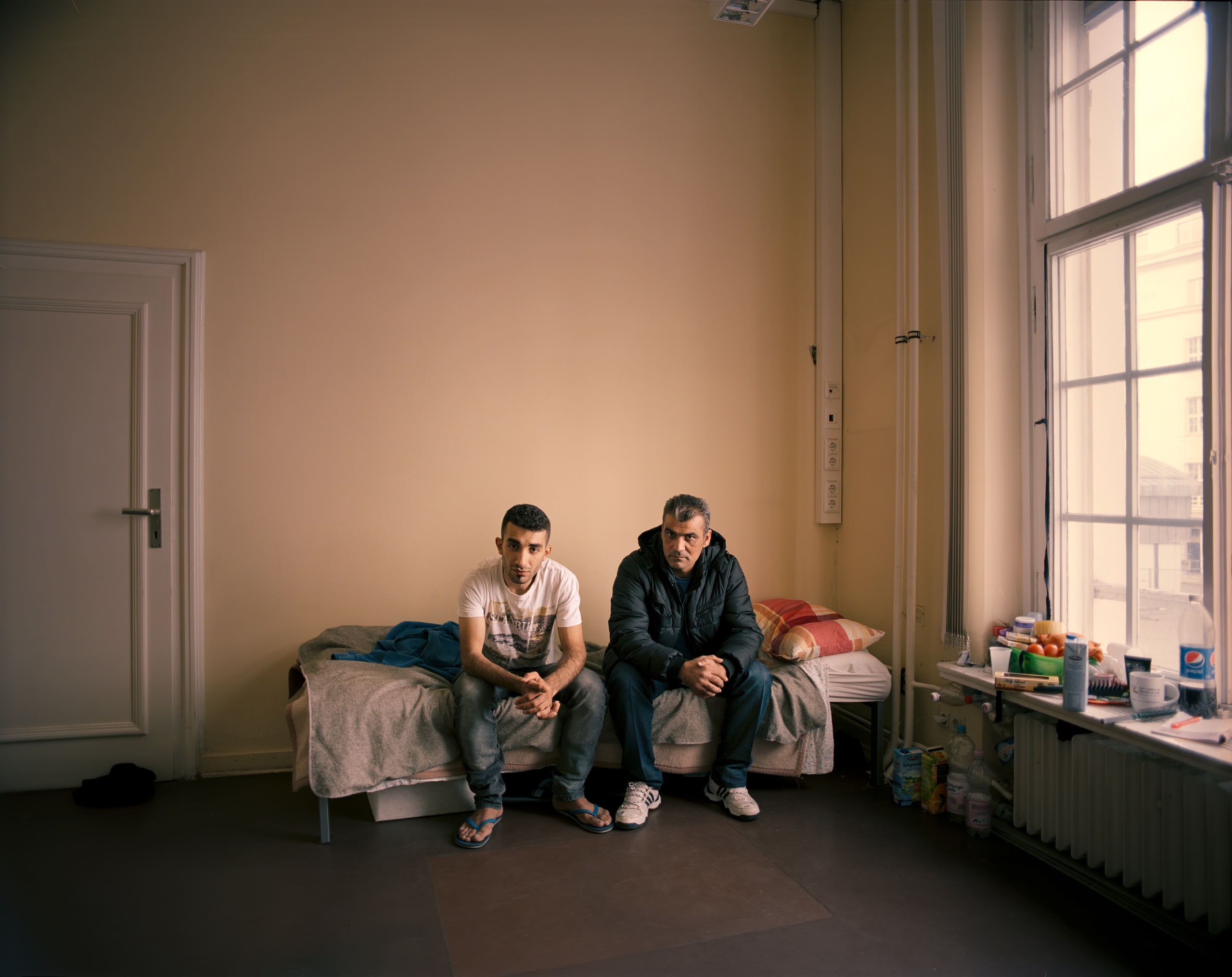 "Alaa Maaz, 23, left, with his cousin, Ibrahim Maaz, 35, in the Wilmersdorf refugee shelter in Berlin. Both men are from Aleppo, Syria and have yet to receive their asylum papers.                                                              ""In Syria before the war, I was very happy. Nothing was missing from my life,  says Ibrahim.  Now everything is gone, my brother is gone. My mother is in a small village near the border called Bab al-Hawa, which isn't that safe. She can't walk so she can't go to Turkey. All I want to know is how I can bring my wife and family here from Turkey. Nobody tells me about the procedures.""                                                              ""Of course I want to stay here and build my life,  Alaa says.  There is no hope to go back home."