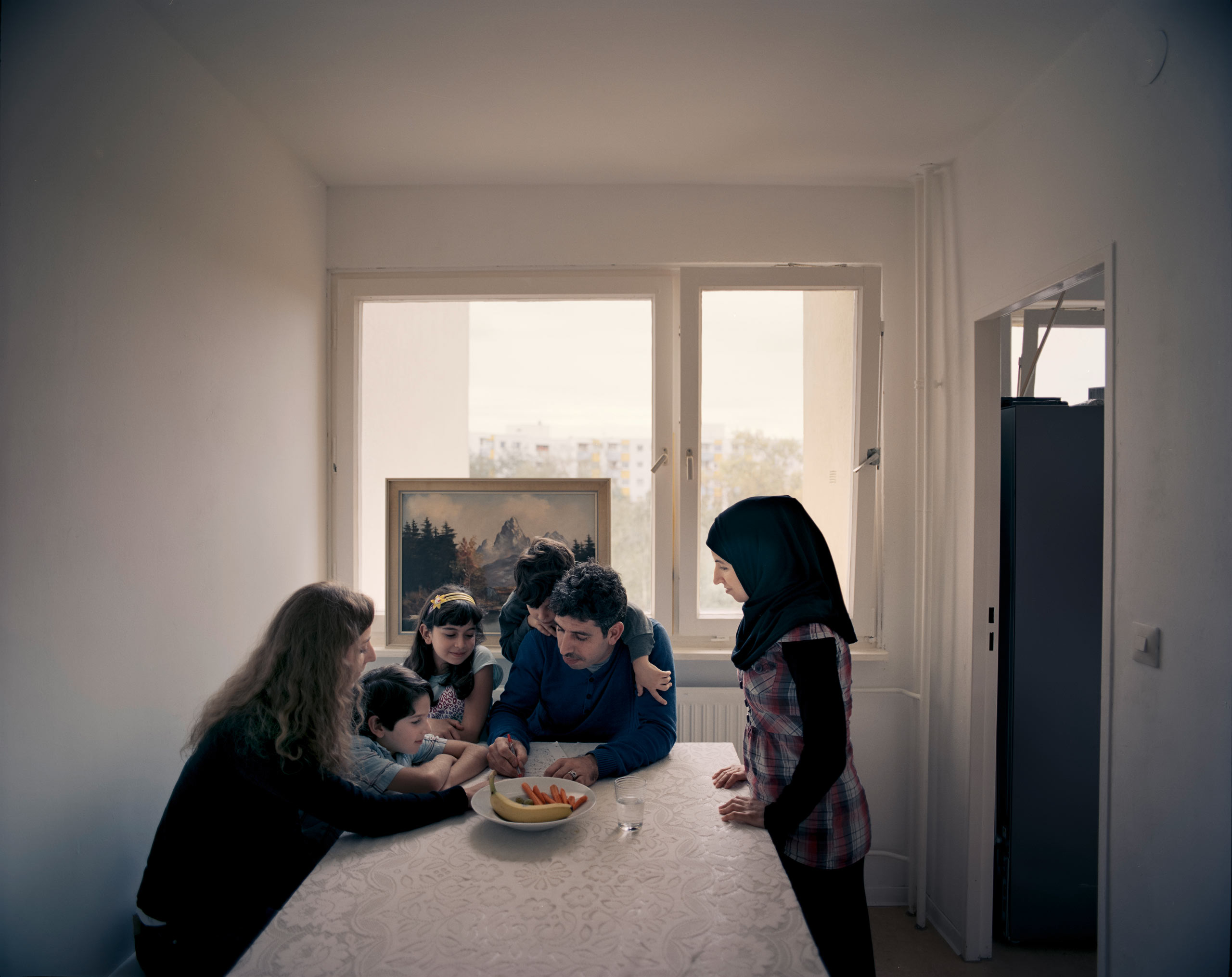"""Britta Leben, left, a 27-year-old German master's student, helps Zakaria Edelbi, 30, center, with                               his German-language work. Edelbi came to Berlin in August 2014, leaving behind his wife and three                               children in Aleppo, Syria. He was reunited with them in March 2015 after months of trying to secure visas.                                                               Leben first met Edelbi in May thanks to Beginn Nebenan Berlin, an organization that connects locals with refugees. """"I just wanted to get to know the people we're sharing this city with,"""" she says.                               """"And Zakaria's family is so open-minded and fun to be around."""" In late August, the Edelbis moved out of a shelter and into their own flat in Spandau, West Berlin. The children now attend school nearby and already speak some German. Edelbi says he fears for Syria's future—but for the first time, he is                               no longer afraid for his children."""
