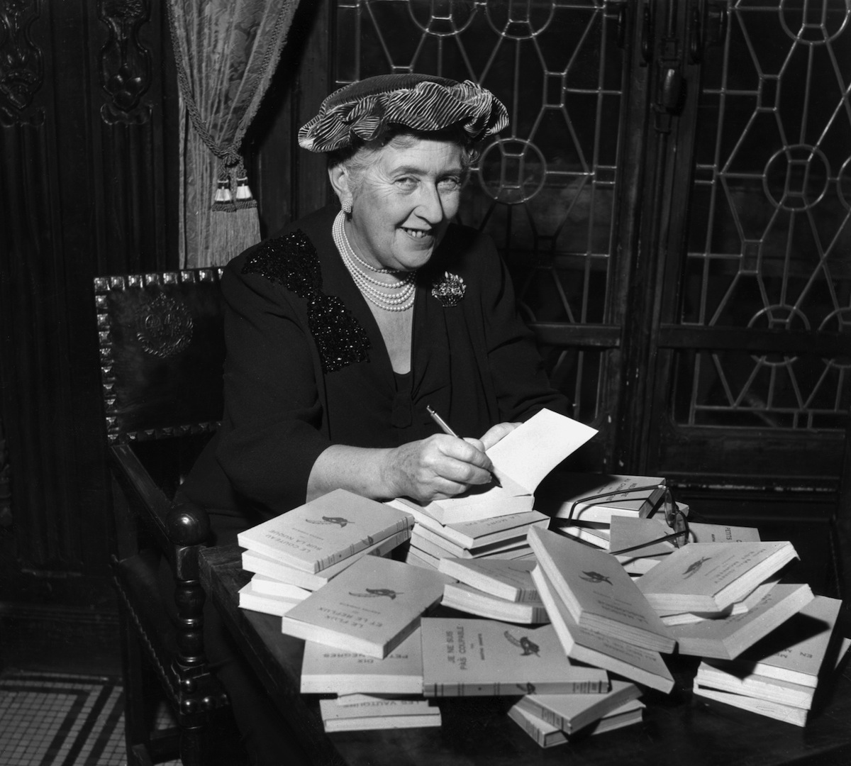 mystery author Agatha Christie (1890-1976) autographing French editions of her books in 1965