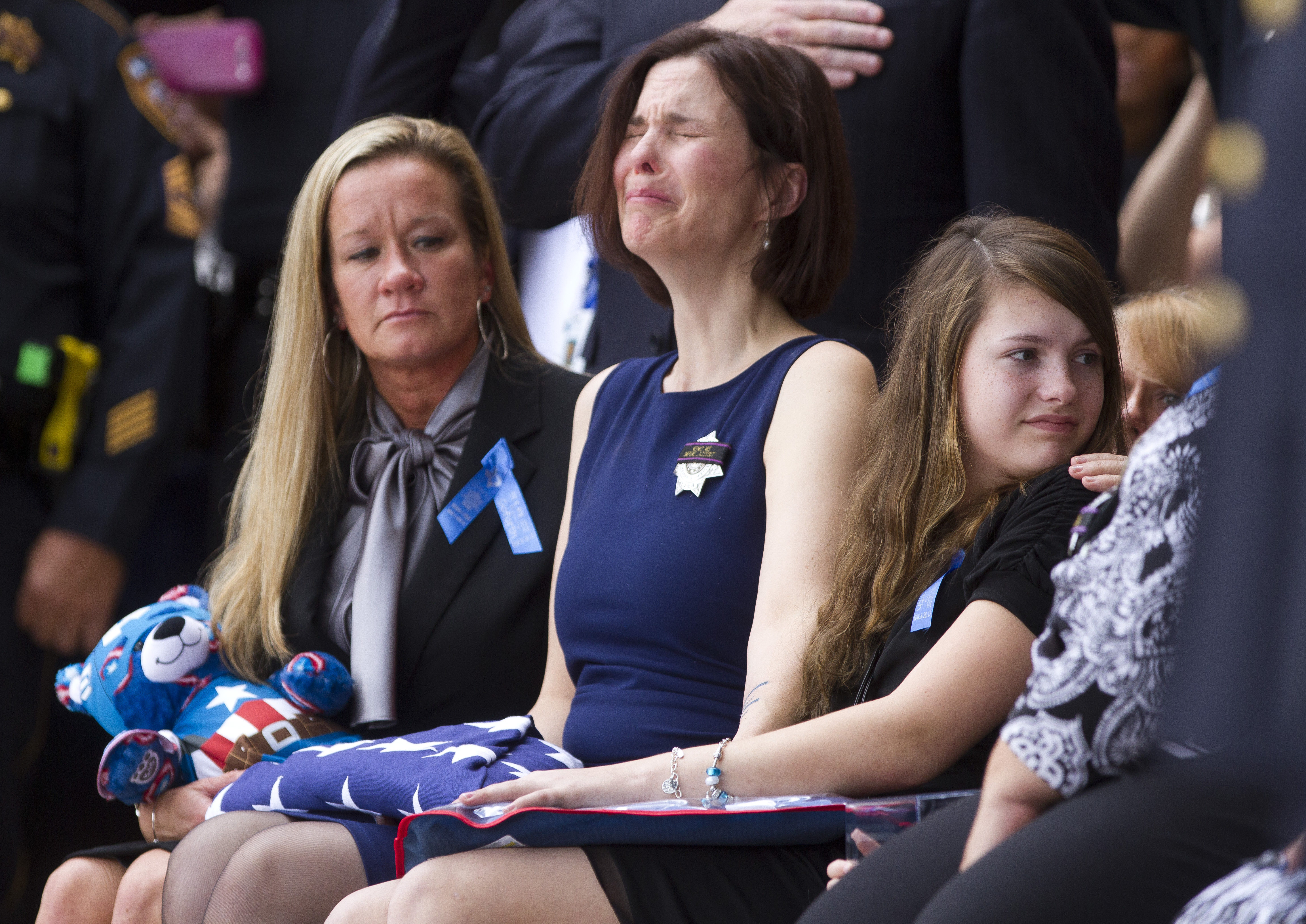 Kathleen Goforth, center, reacts as a 21-gun salute sounds off during the funeral service for her husband Harris County Sheriff's Deputy Darren Goforth at Second Baptist Church in Houston on Sept. 4, 2015
