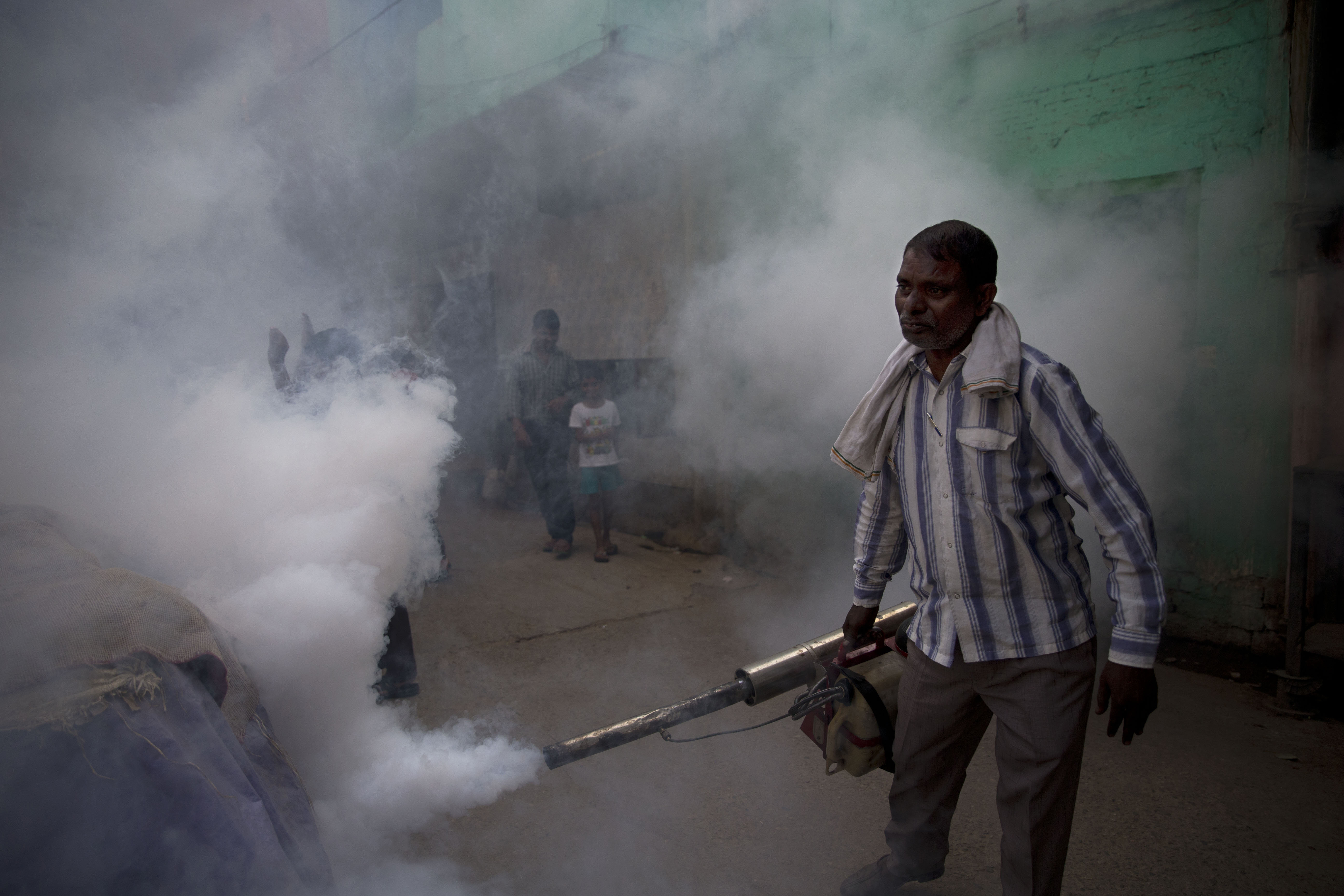 A municipal worker fumigates a residential area to prevent mosquitoes from breeding in New Delhi on Sept. 7, 2015