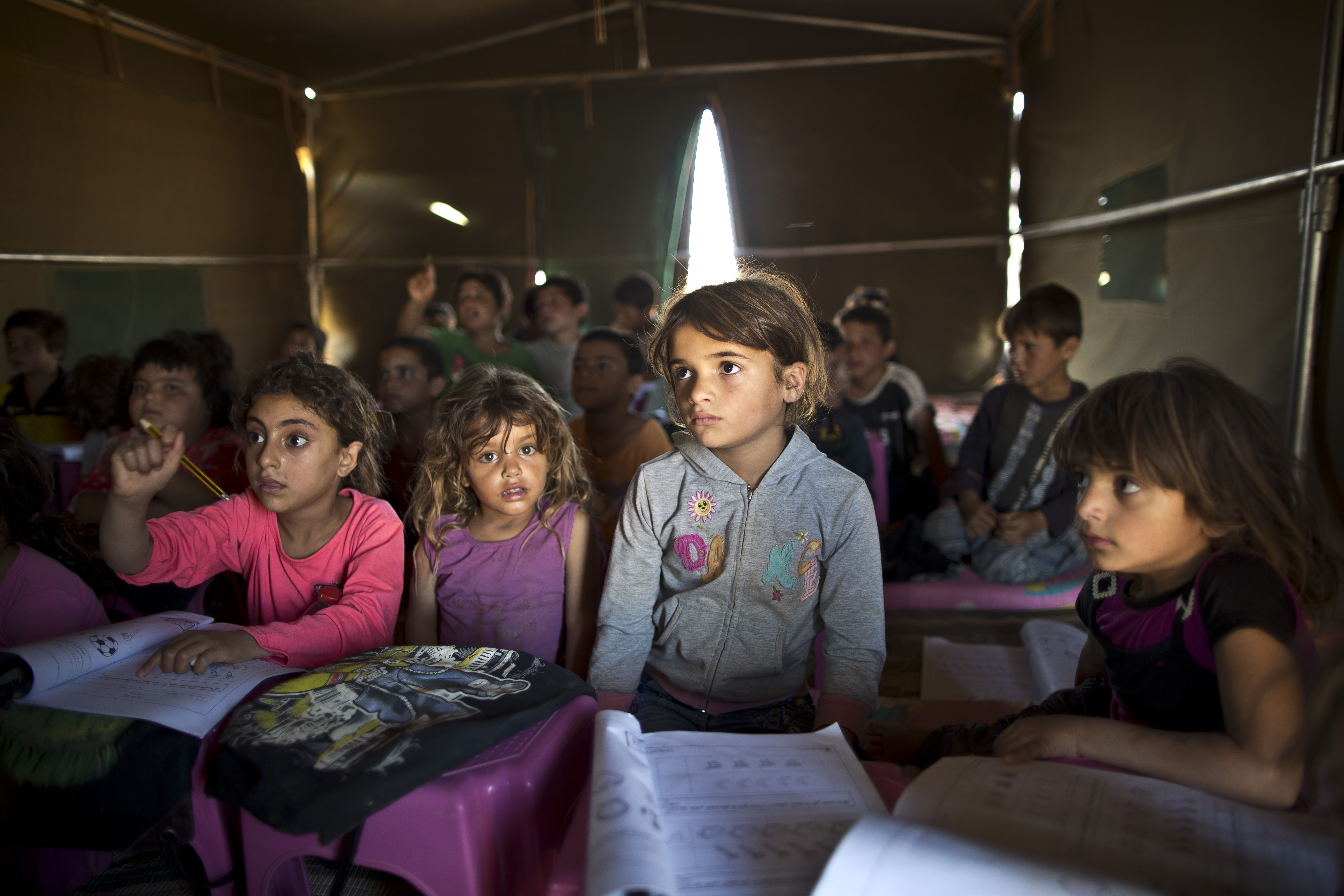 In this Aug. 11, 2015, file photo, Syrian refugee children attend a class at a makeshift school set up in a tent at an informal settlement near the Syrian border on the outskirts of Mafraq, Jordan. Forty percent of children from five conflict-scarred Middle Eastern countries are not in school, the U.N. child-welfare agency said in a report on Sept. 3, 2015
