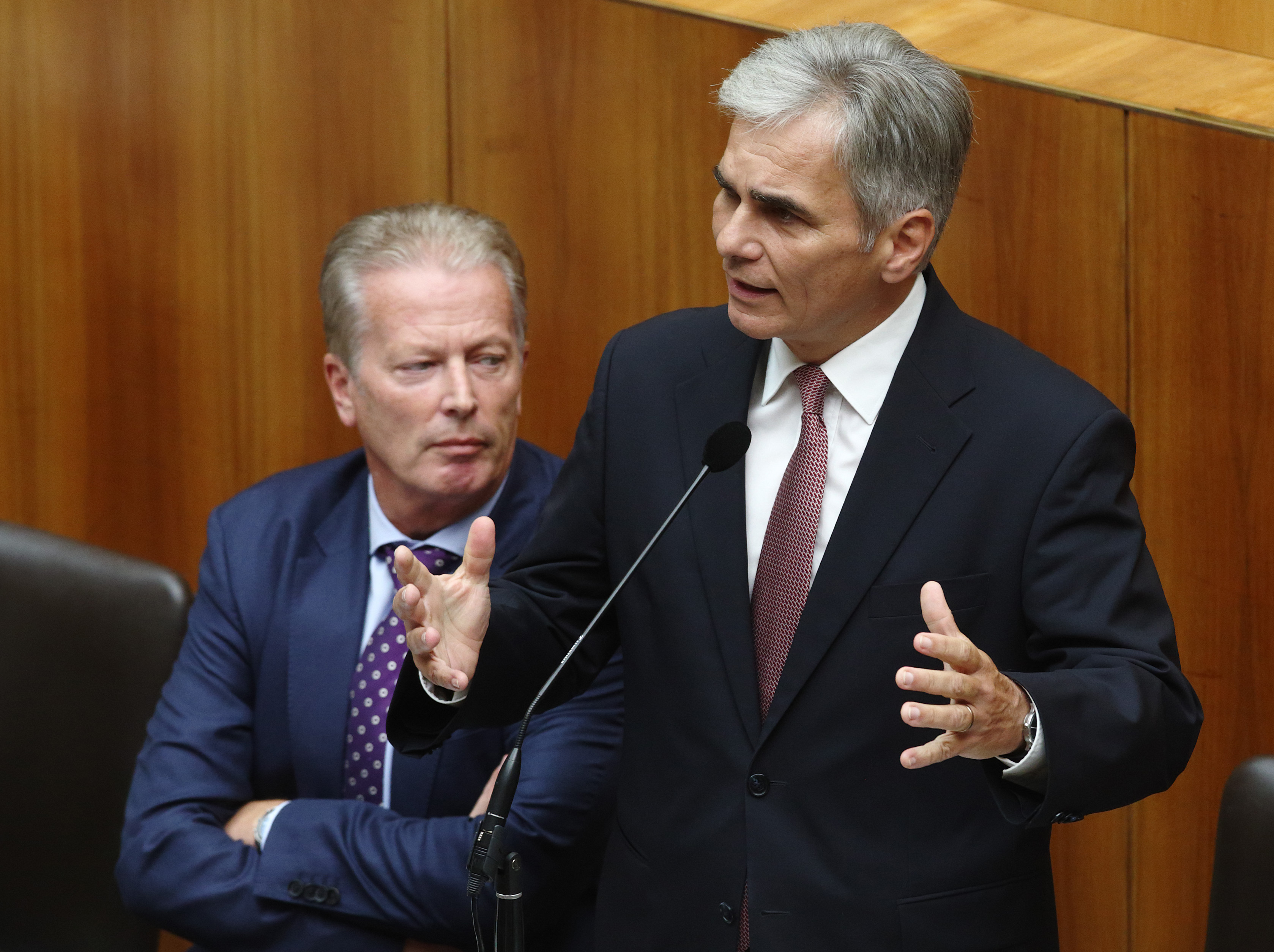Austrian Chancellor Werner Faymann (R) talks next to Vice Chancellor Reinhold Mitterlehner during an extraordinary session of the parliament on migration policy in Vienna on Sept. 1, 2015.