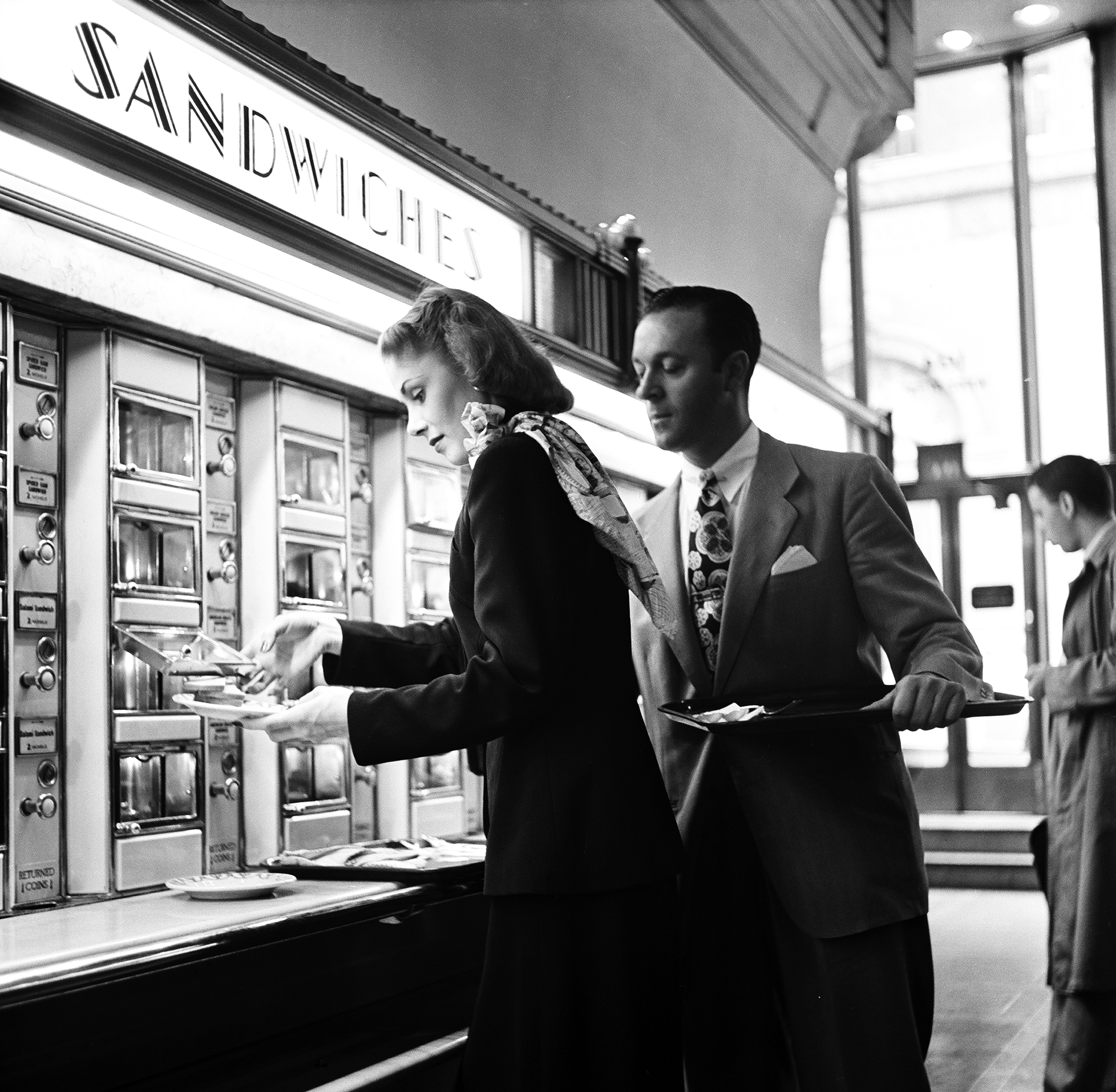 View of a well-dressed man and woman deciding on sandwiches at Grand Central Station automat in New York, 1948.