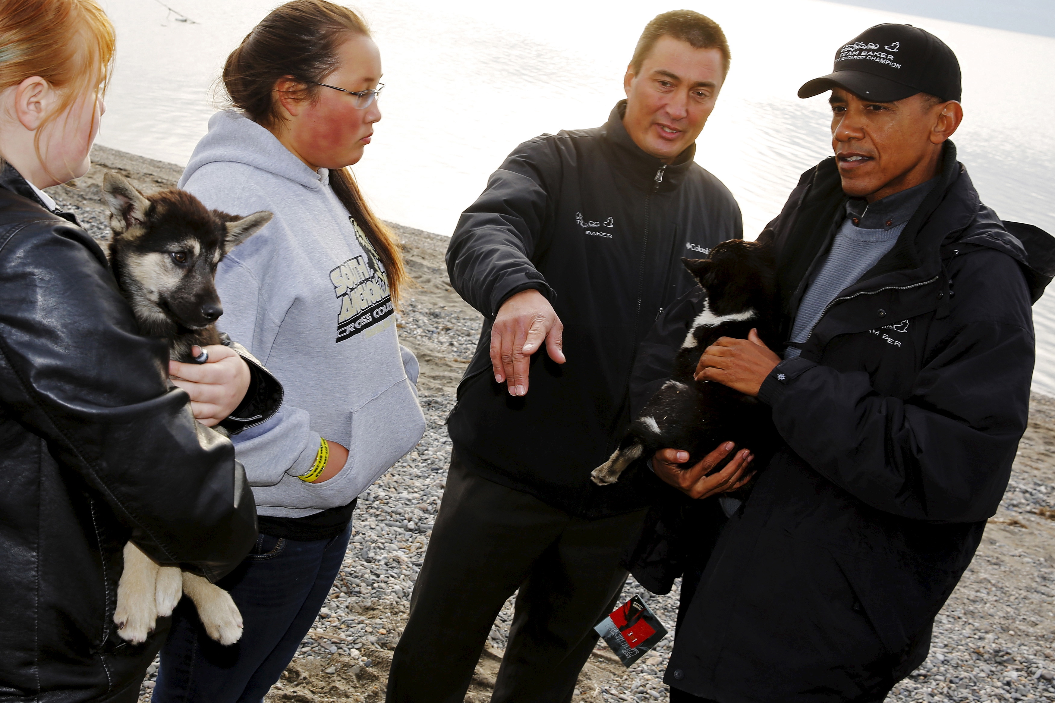 U.S. President Barack Obama (R) looks at dog sled puppies belonging to 2011 Iditarod Dog Sled Race champion John Baker in Kotzebue, Alaska on Sept. 2, 2015.