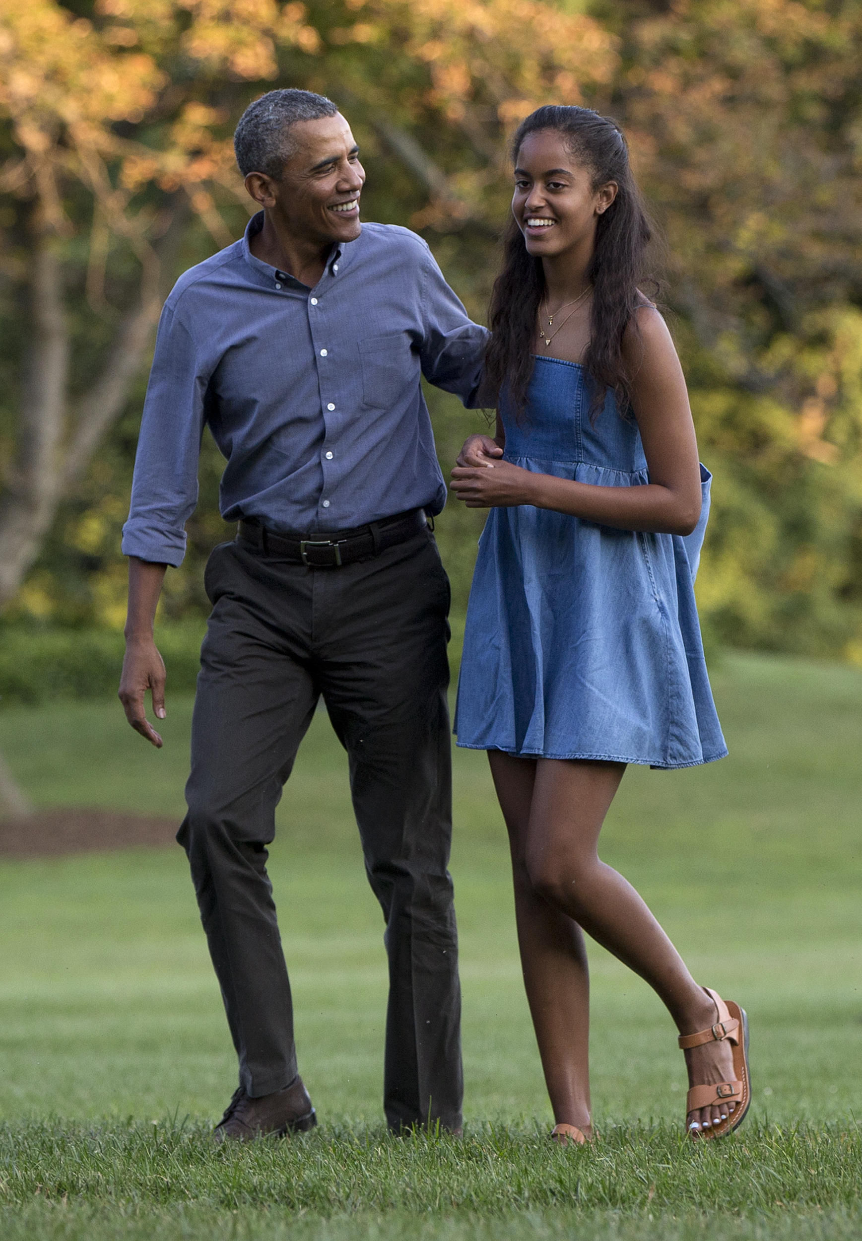 President Barack Obama and his daughter Malia walk across the South Lawn of the White House in Washington on Aug. 23, 2015.