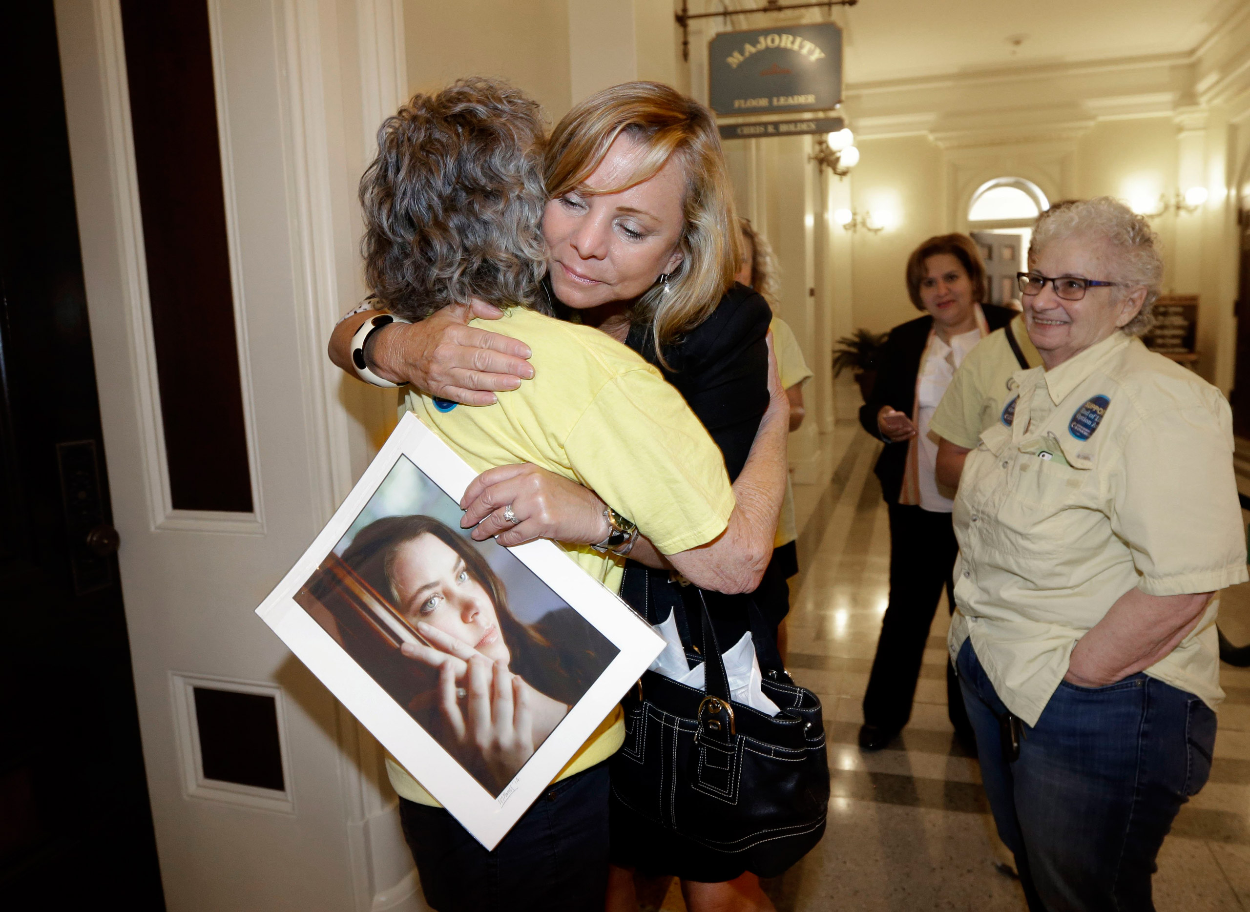 Debbie Ziegler holds a photo of her daughter, Brittany Maynard, as she receives congratulations from Ellen Pontac, after a right-to die measure was approved by the state Assembly, in Sacramento, Calif., on Sept. 9, 2015.