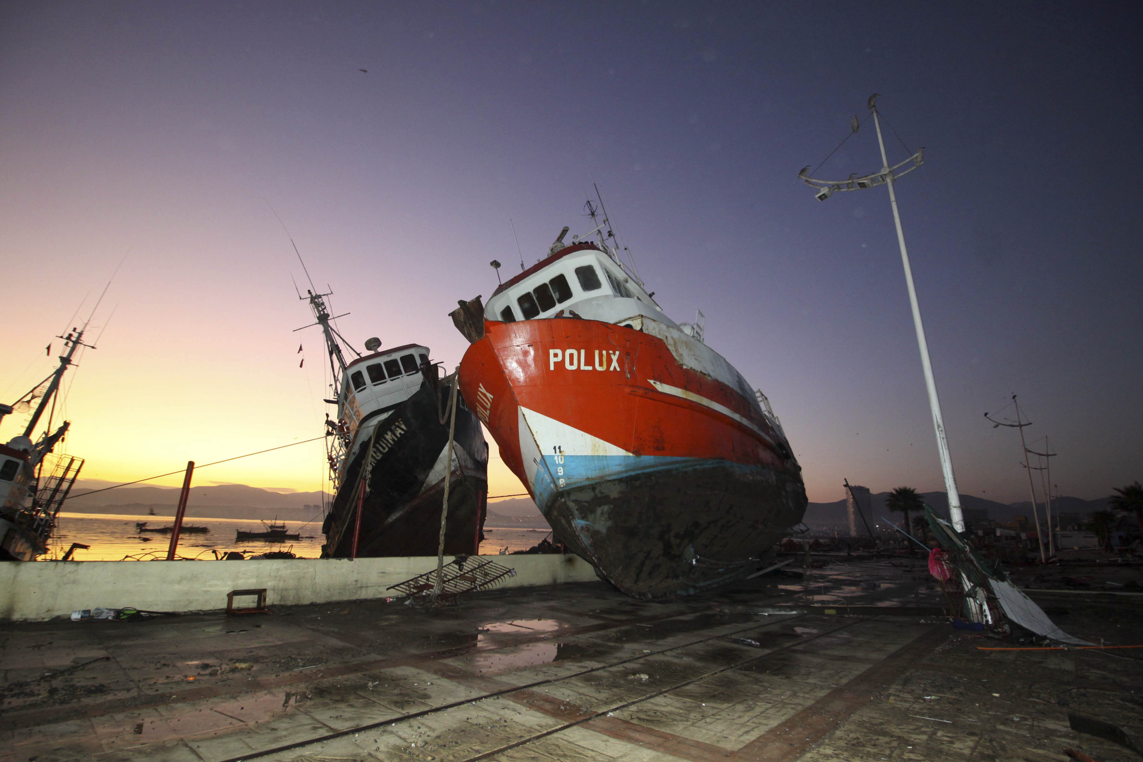 A boat stands on a dock after it was lifted by an earthquake-triggered tsunami in Coquimbo, Chile, Thursday, Sept. 17, 2015. Several coastal towns were flooded from small tsunami waves set off by late Wednesday's magnitude-8.3 earthquake, which shook the Earth so strongly that rumbles were felt across South America.