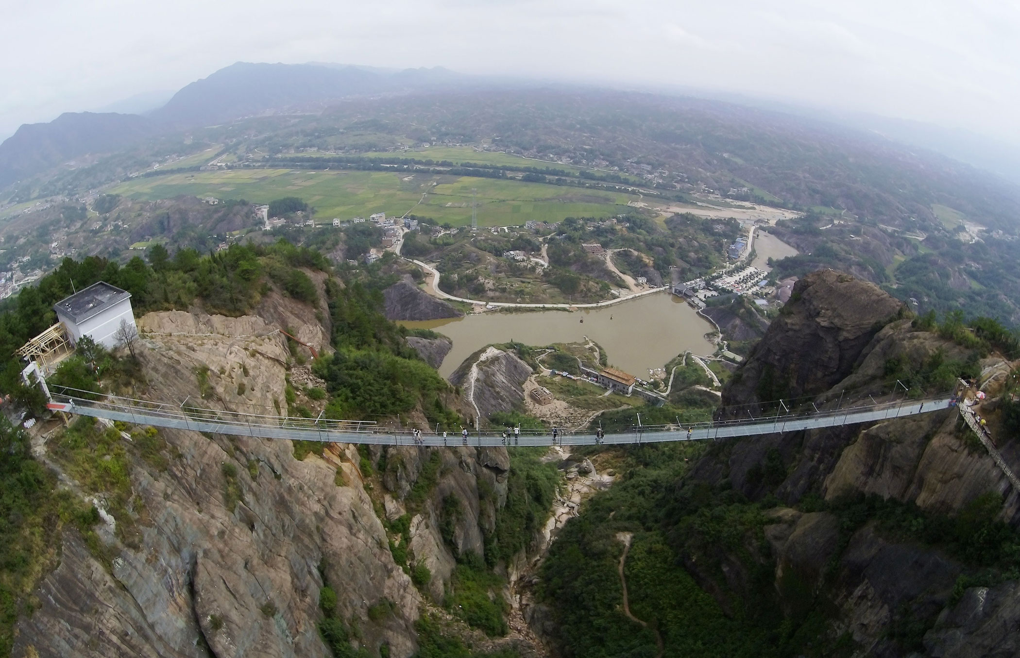 Tourists walk on a 300-meter-long glass suspension bridge at the Shiniuzhai National Geological Park in Pingjiang County, China, on Sept. 24, 2015.
